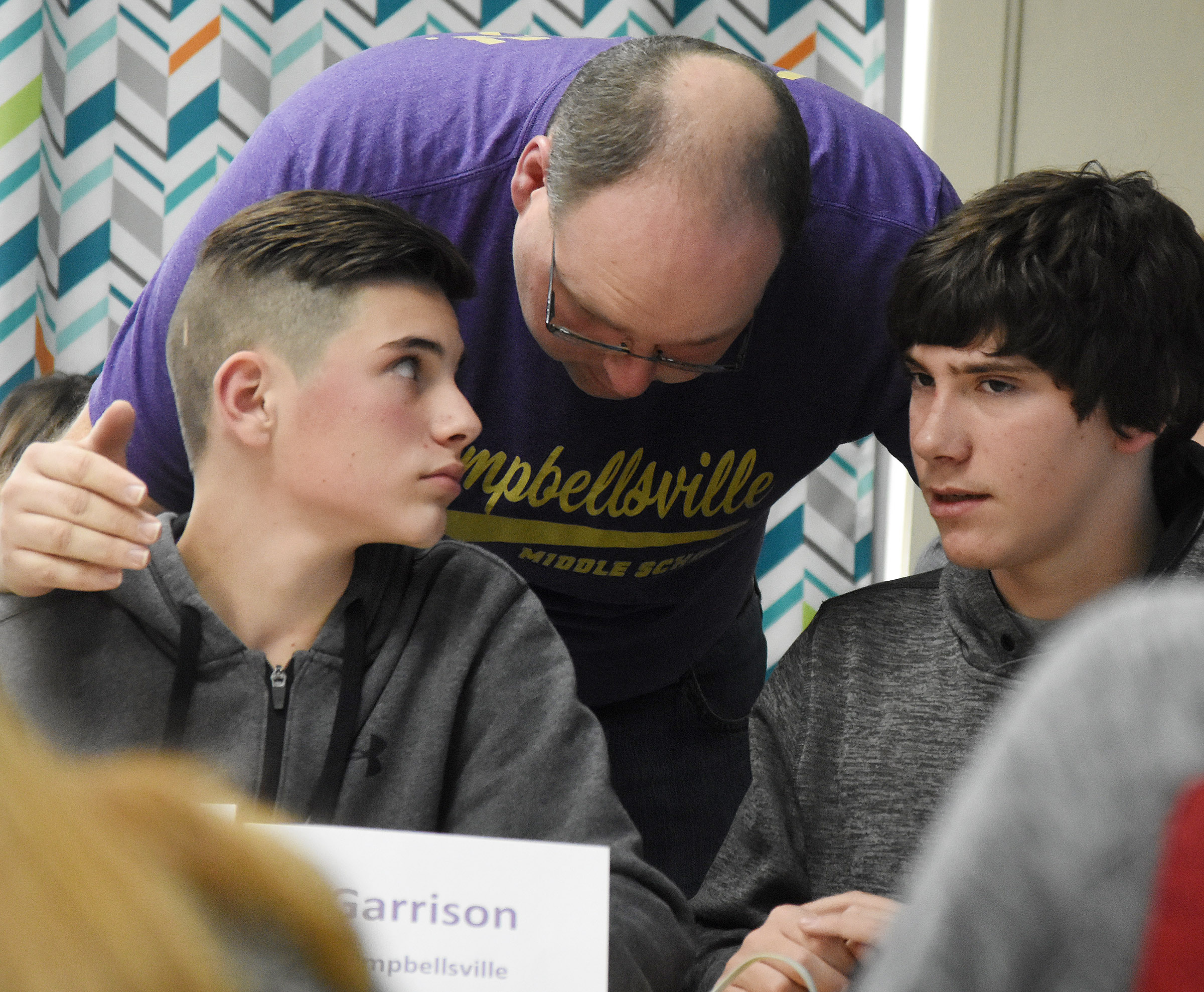 CMS academic team coach Steven Gumm talks to sixth-grader Isaac Garrison, at left, and eighth-grader Peyton Dabney during a quick recall match.
