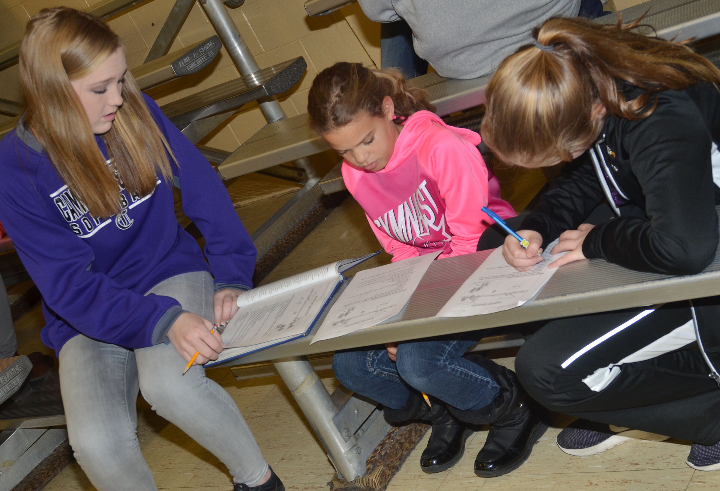 CMS eighth-grader Catlyn Clausen, at left, works with fifth-graders Arisha Francis, center, and Ava Hughes to answer questions about the American Revolution.