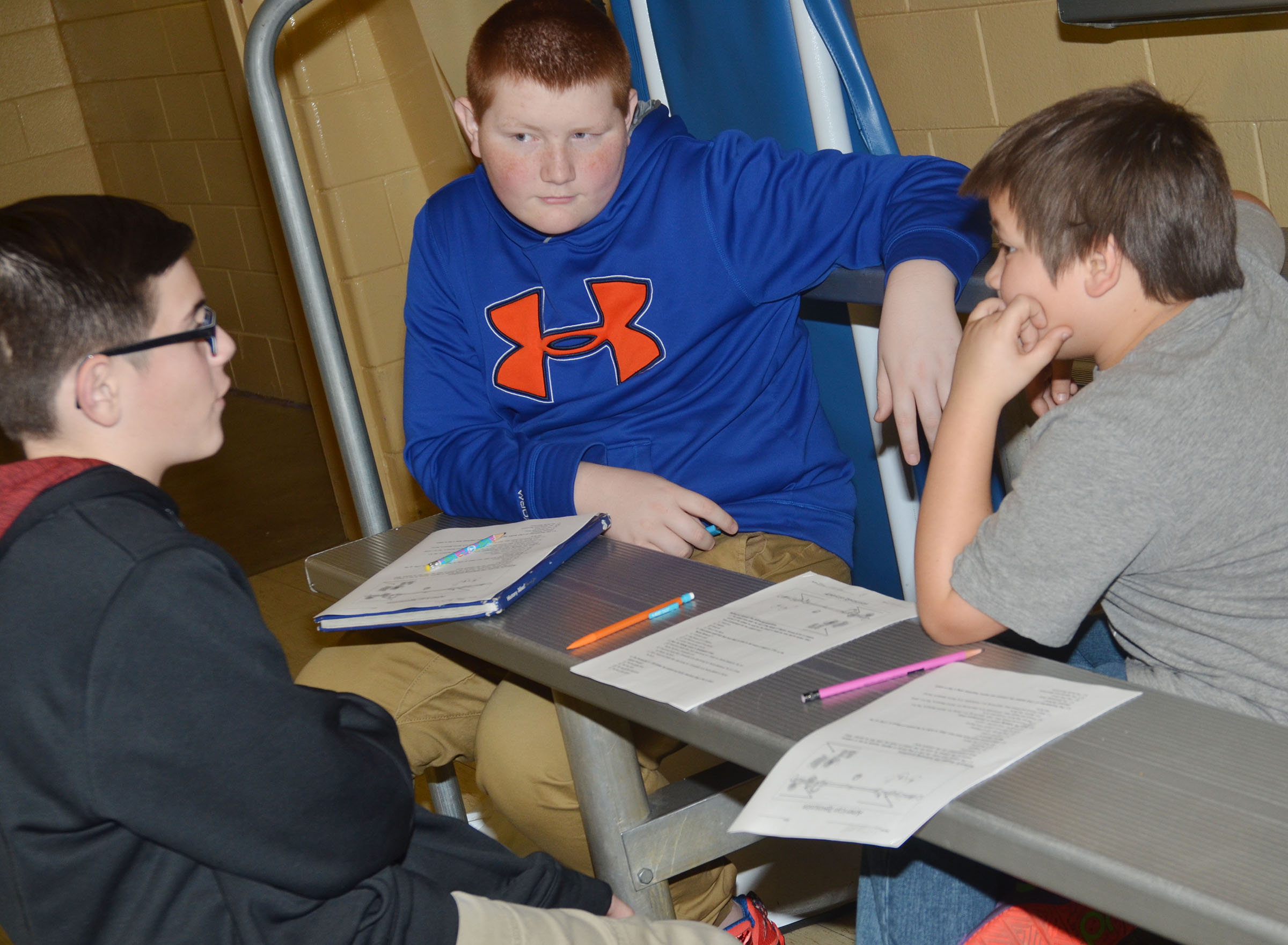 CMS fifth-graders Isaac Garrison, at left, and Leo Lamer, at right, work with eighth-grader Blake Perkins.