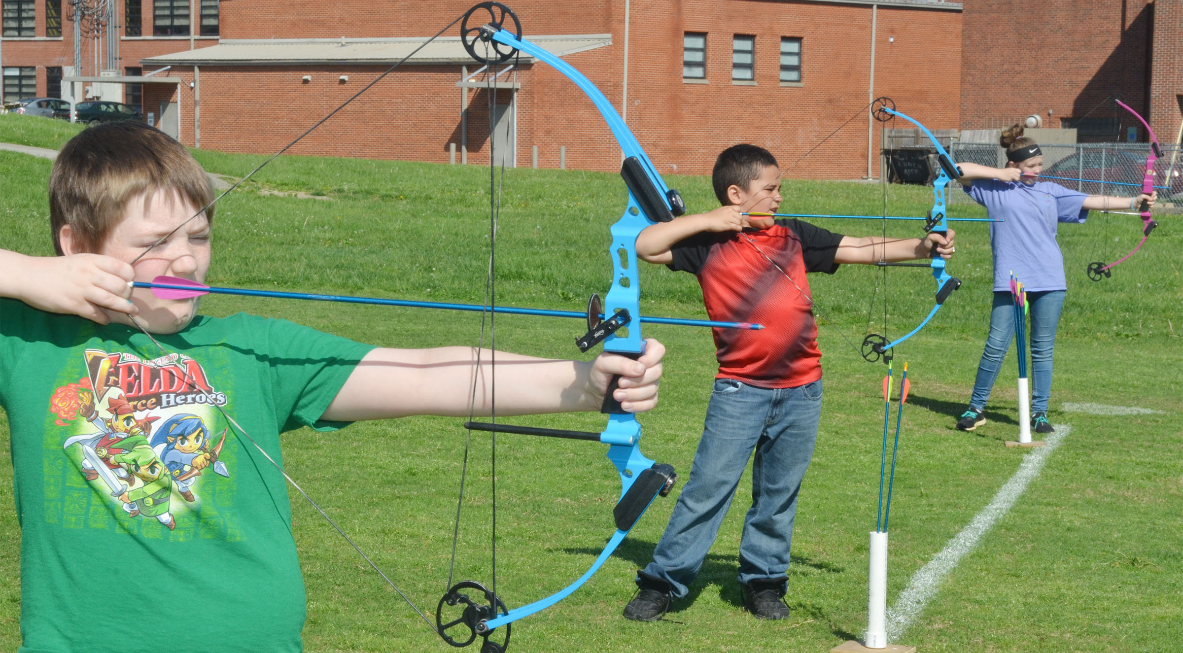 From left, CMS fifth-grader Sully Streeval, fourth-grader Marcus Taylor and fifth-grader CheyAnn Edwards shoot their bows and arrows.