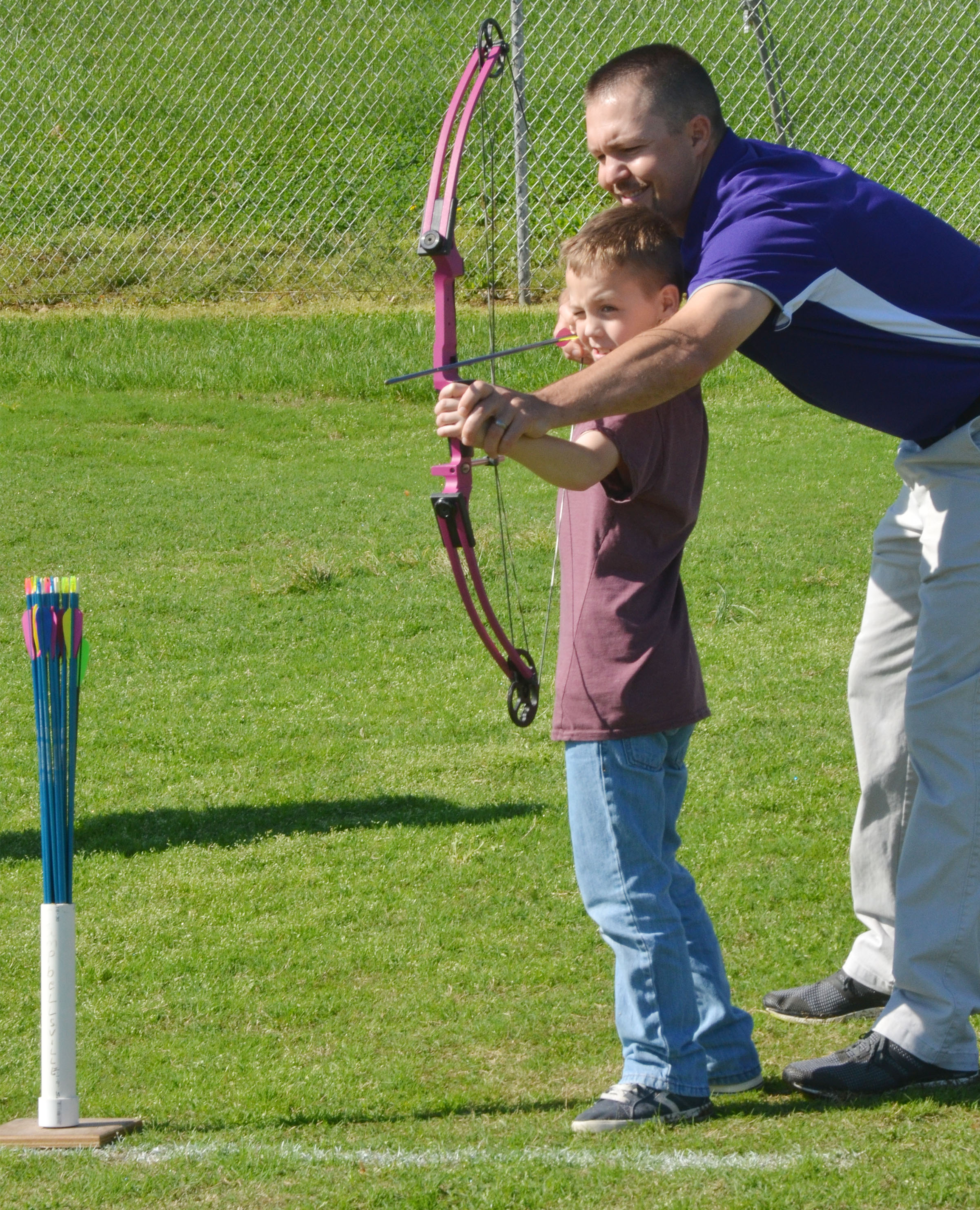 CMS physical education teacher Weston Jones helps fourth-grader Spencer Bates take aim.