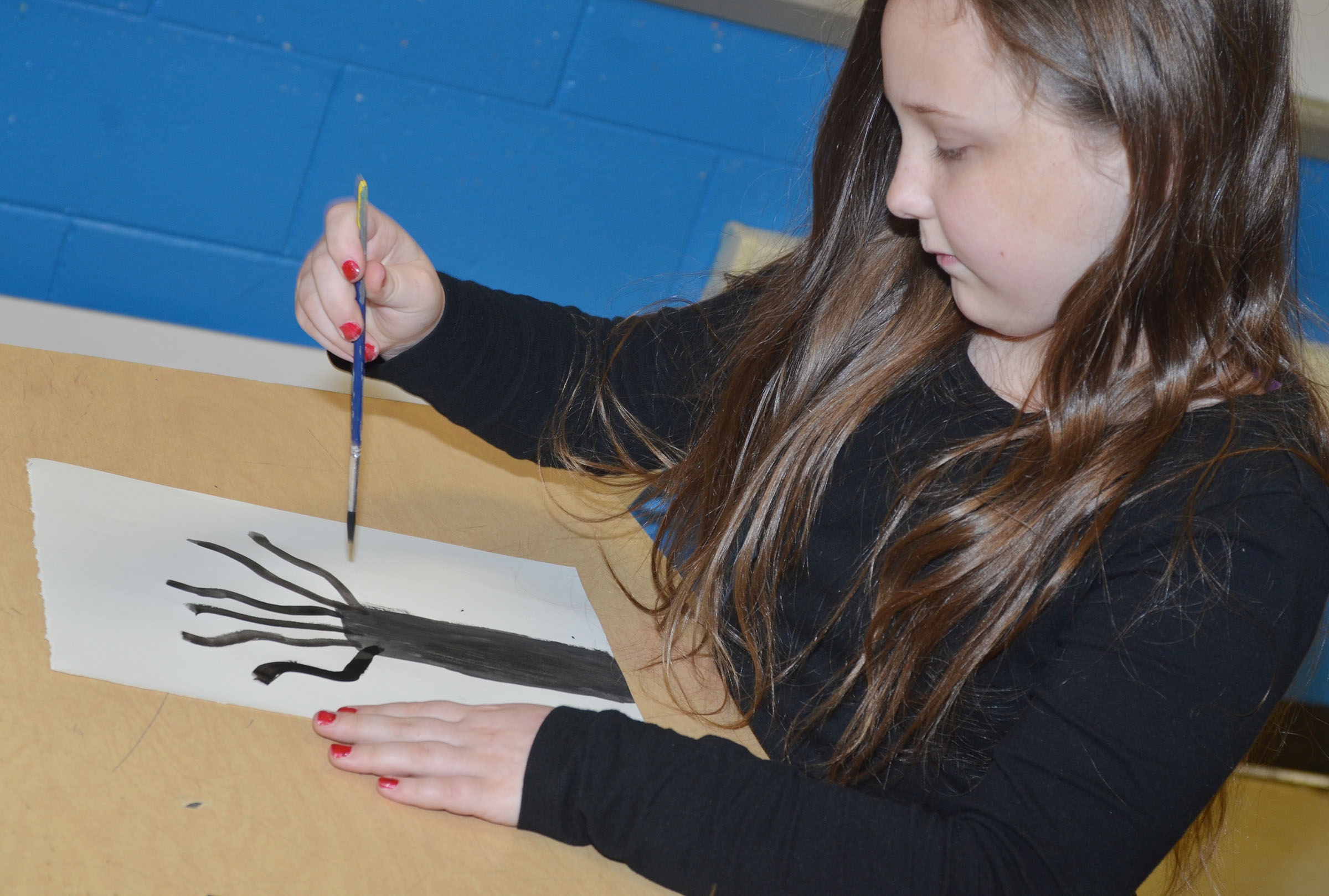 CMS fourth-grader Shyanna Young paints her concentric circle painting.