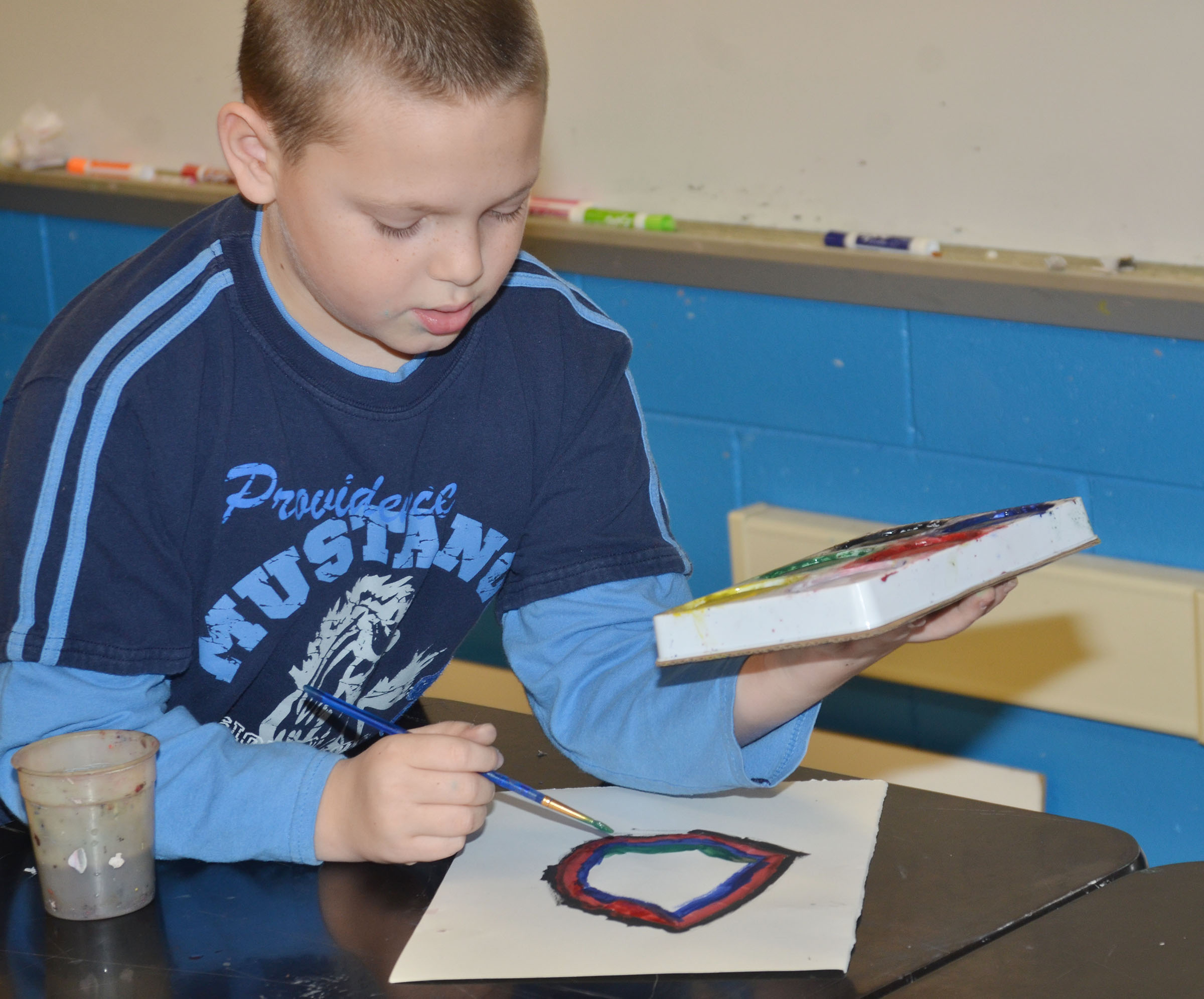 CMS fourth-grader Ethan Marrs paints a concentric circle.