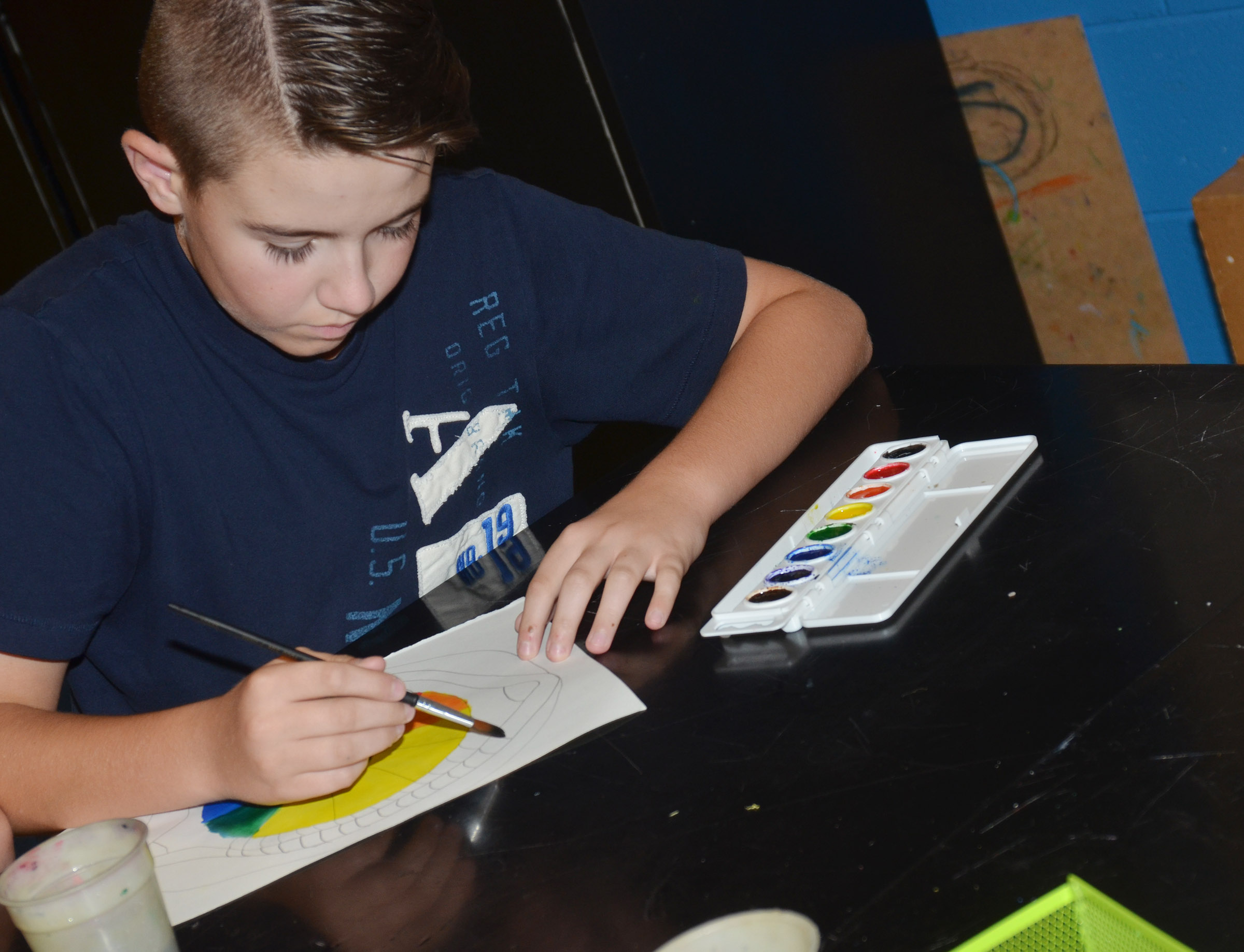 CMS seventh-grader Bryce Newton paints his color wheel.