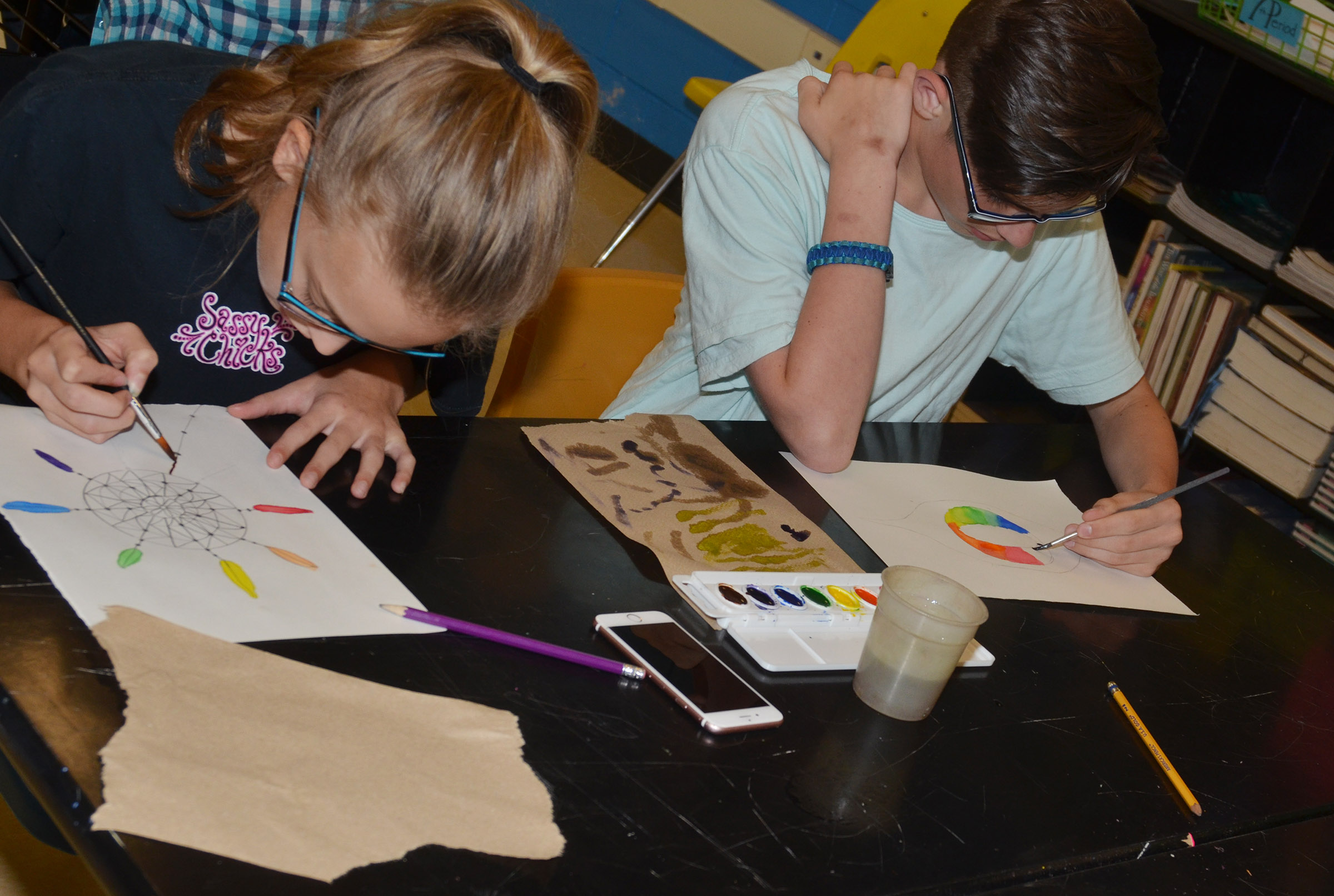 CMS sixth-graders Chloe Thompson, at left, and Isaac Garrison paint their color wheels.