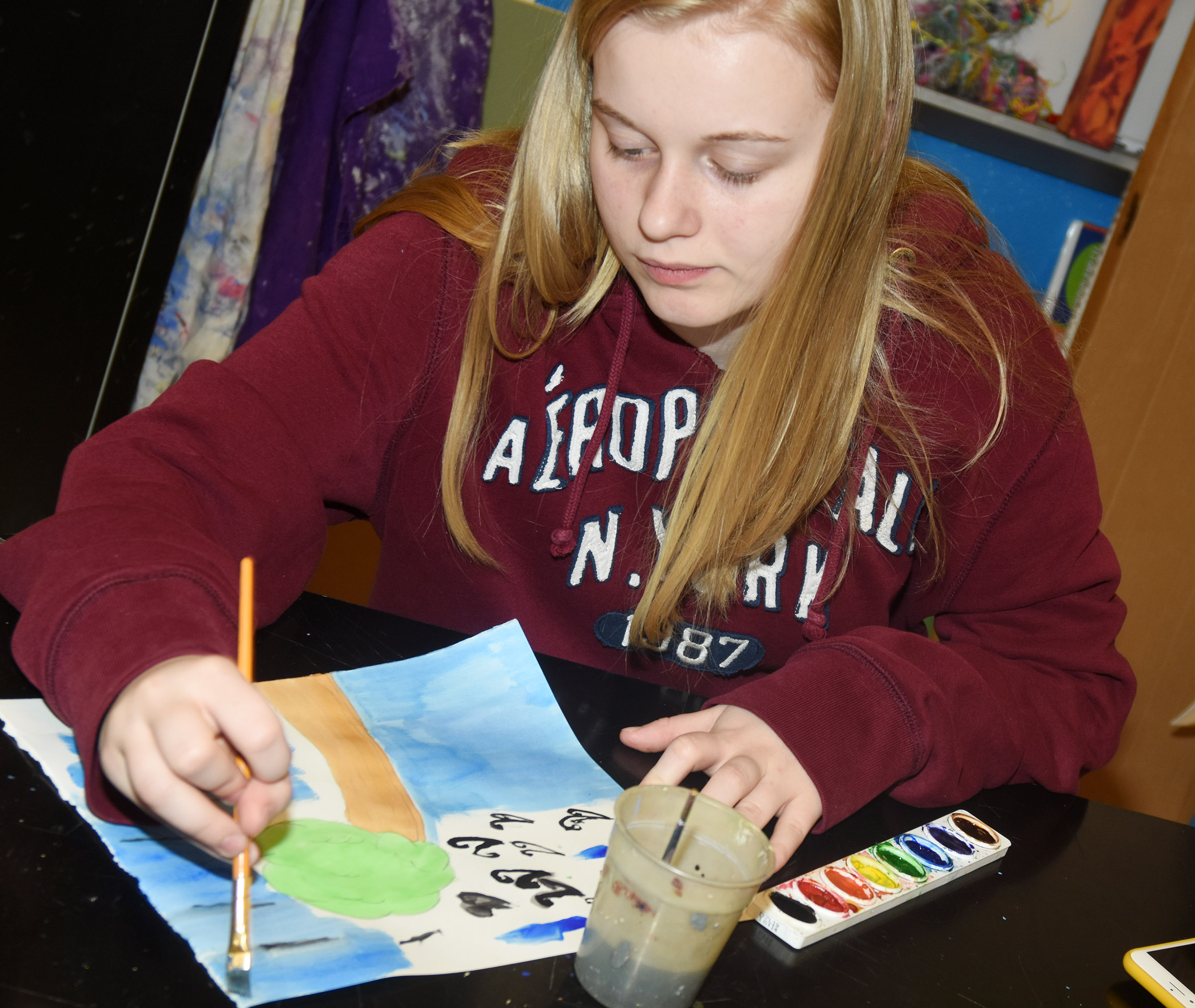 CMS eighth-grader Gabby Skaggs paints an outdoor scene depicting motion.