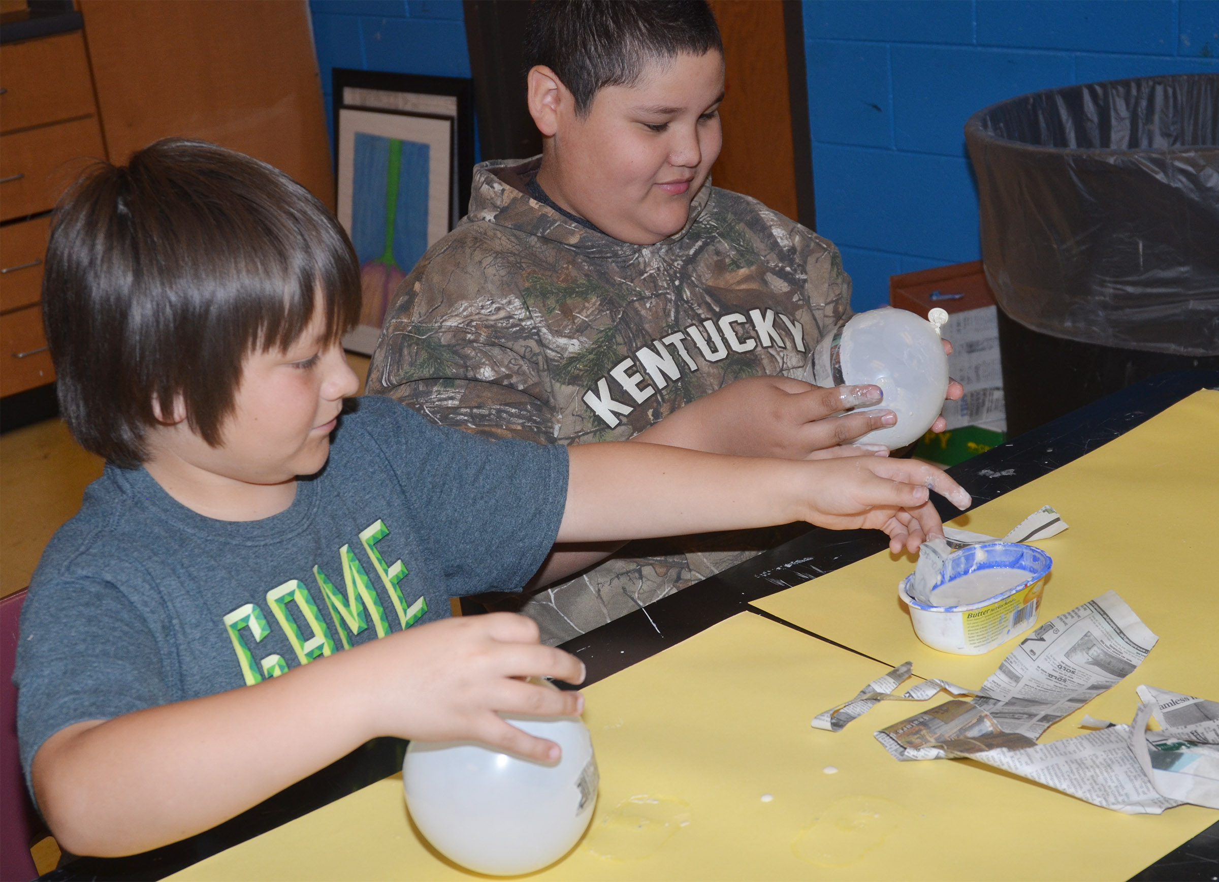 CMS fourth-graders Leo Lamer, at left, and Xavier Florez add paper mache to their balloons, which will become Faberge eggs.