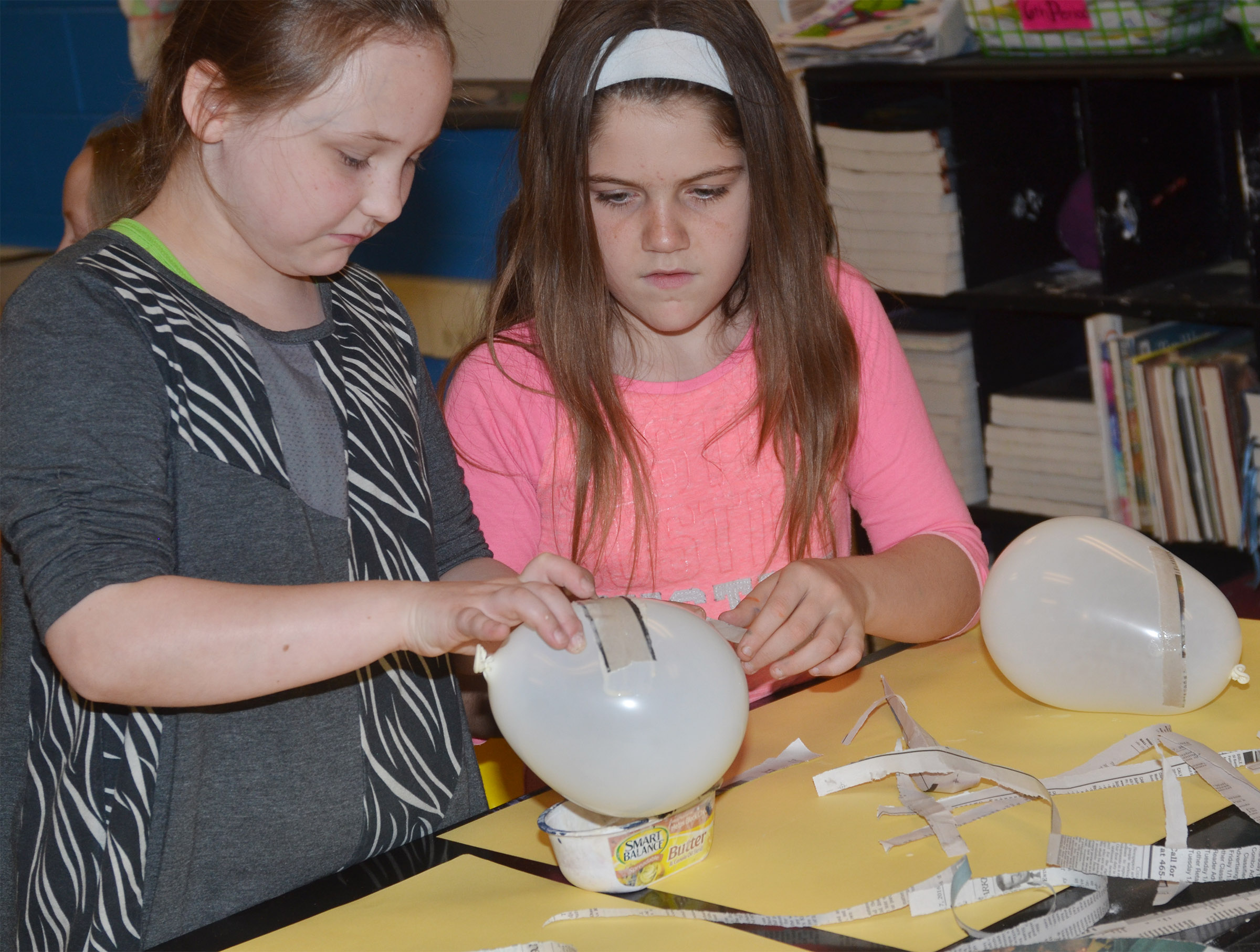 CMS fourth-graders Shyanna Young, at left, and Summer Cothern add paper mache to their balloons, which will become Faberge eggs.