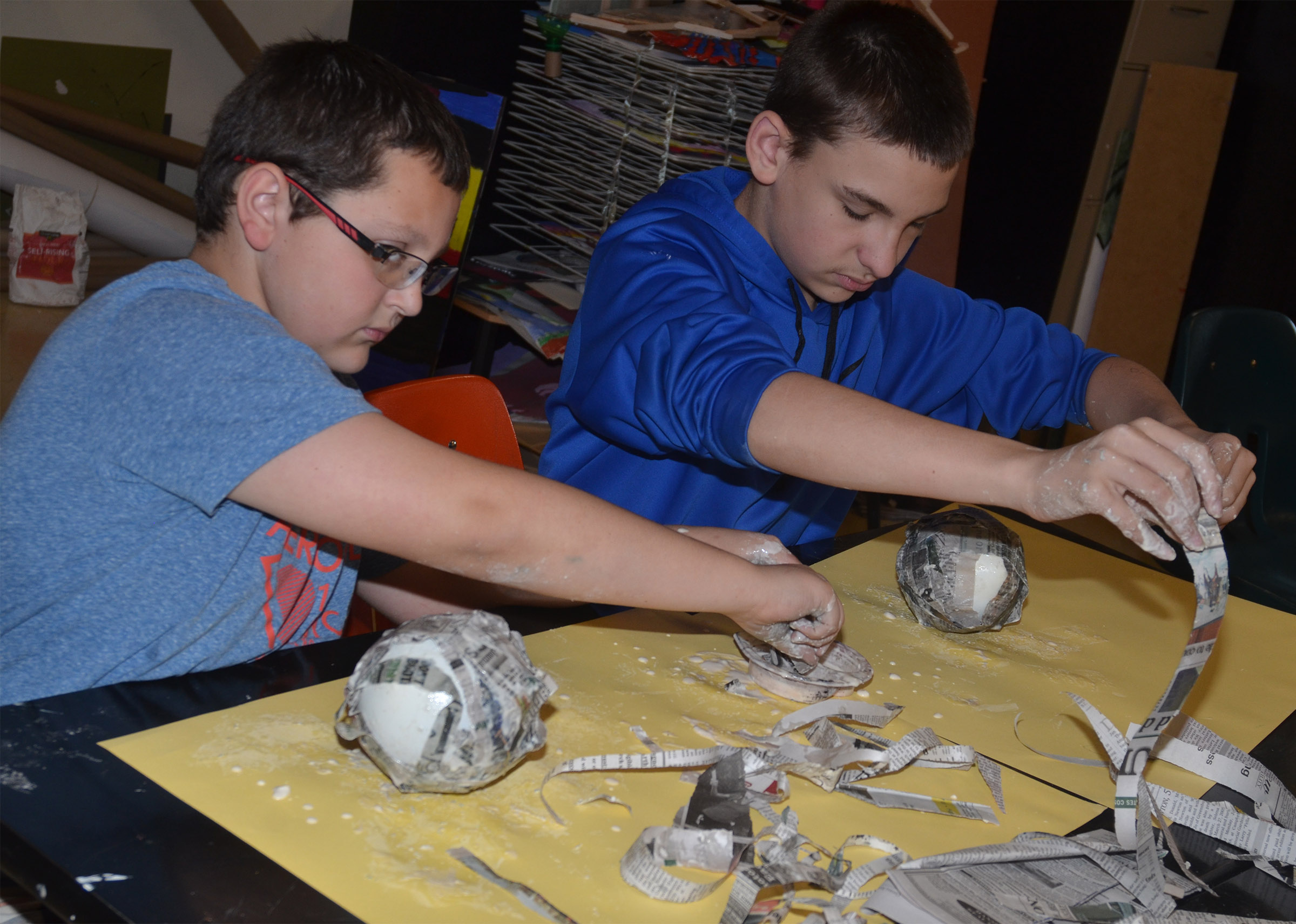 CMS fifth-graders Cameron Mahan, at left, and Nate Mitchell add paper mache to their balloons, which will become Faberge eggs.