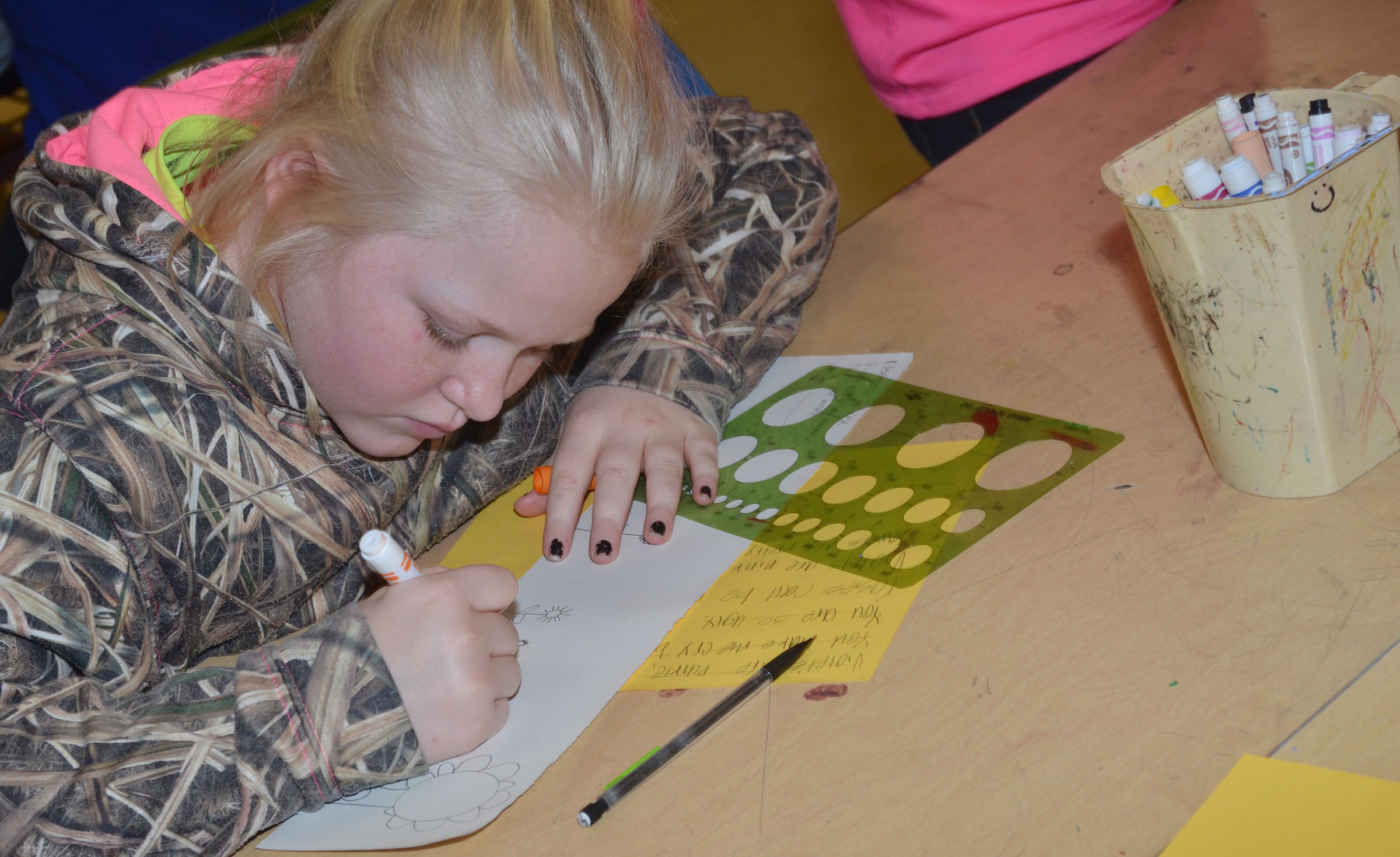 CMS fourth-grader Daisy Wilkerson colors her haiku scroll.