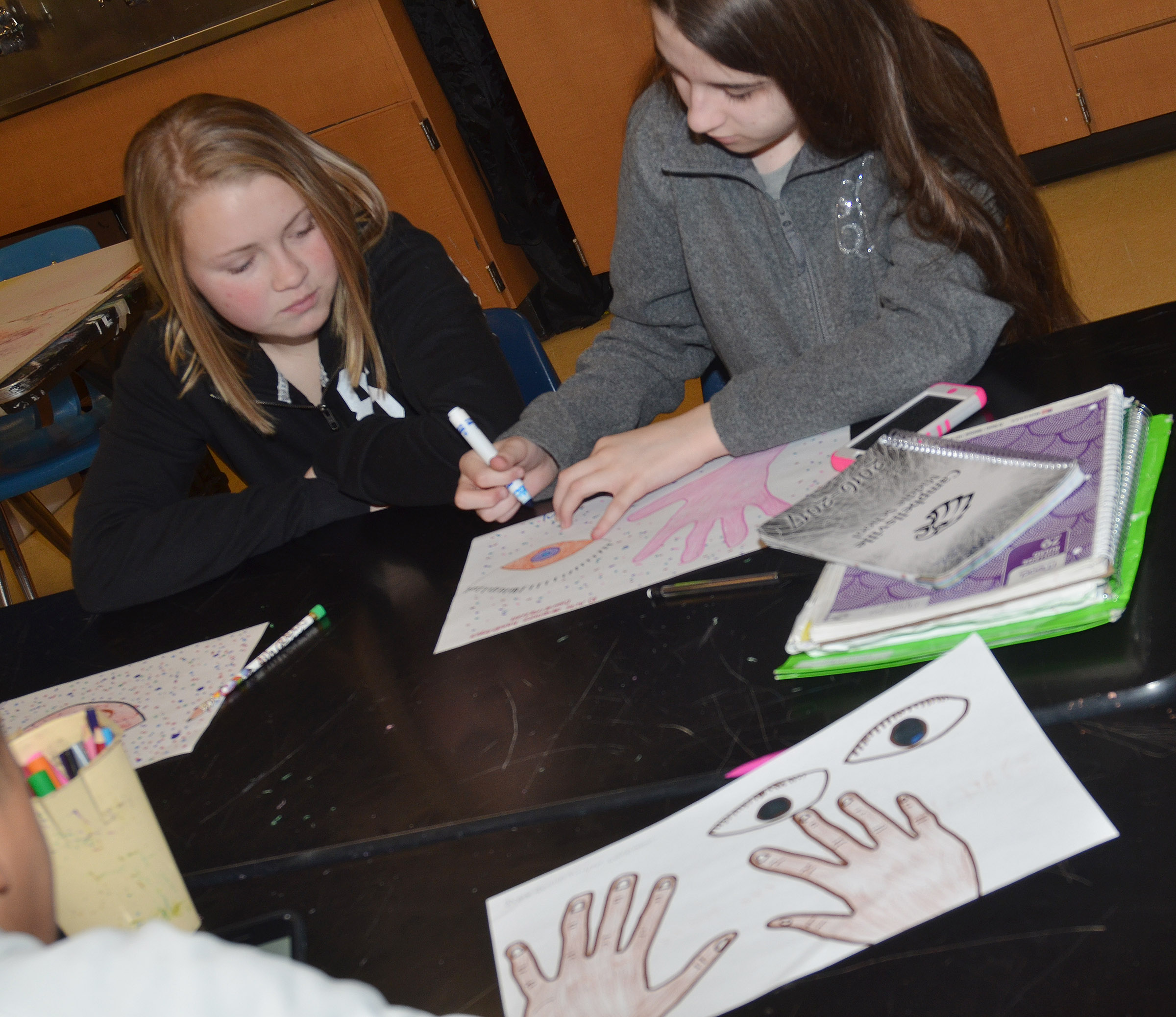 CES eighth-graders Alanna Atwood, at left, and Chloe Cox work on their art work that illustrates why they believe art should be taught in schools.