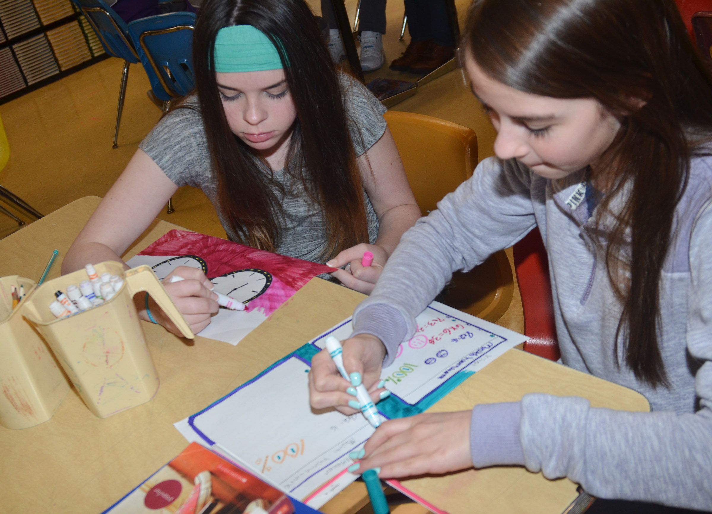 CMS seventh-graders Destiny Agee, at left, and Chloe Anderson work on their artwork that illustrates why they believe art should be taught in schools.