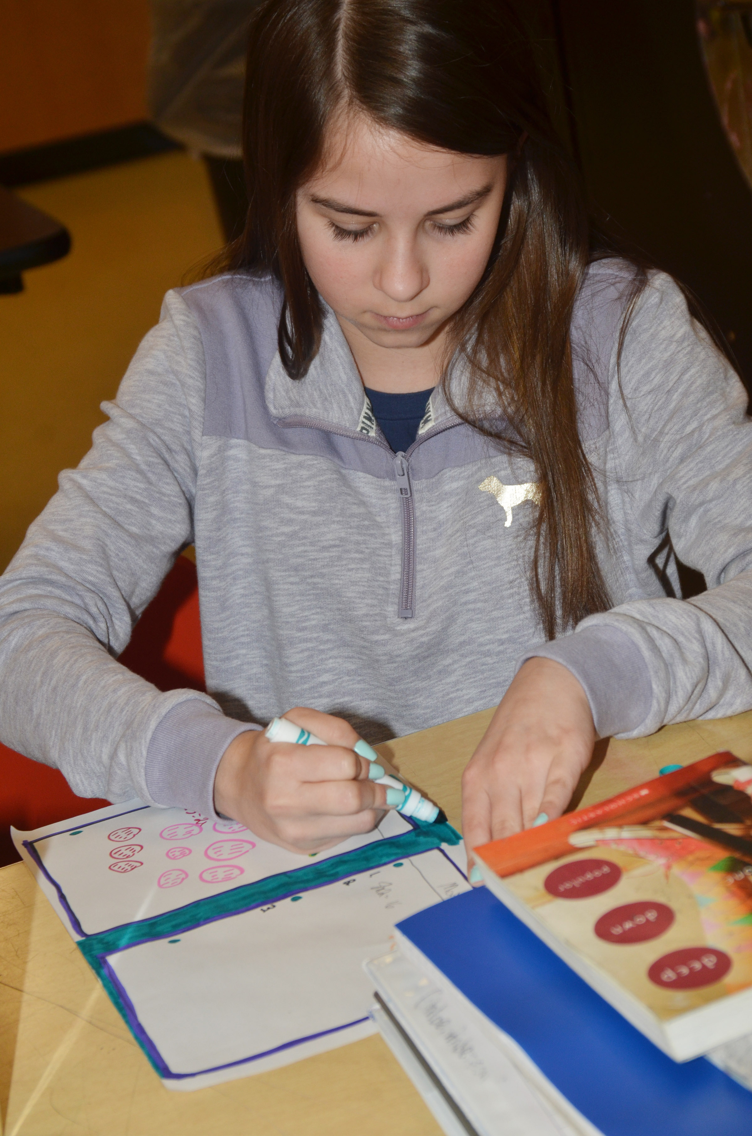 CMS seventh-grader Chloe Anderson colors her artwork that illustrates why she believes art should be taught in schools.