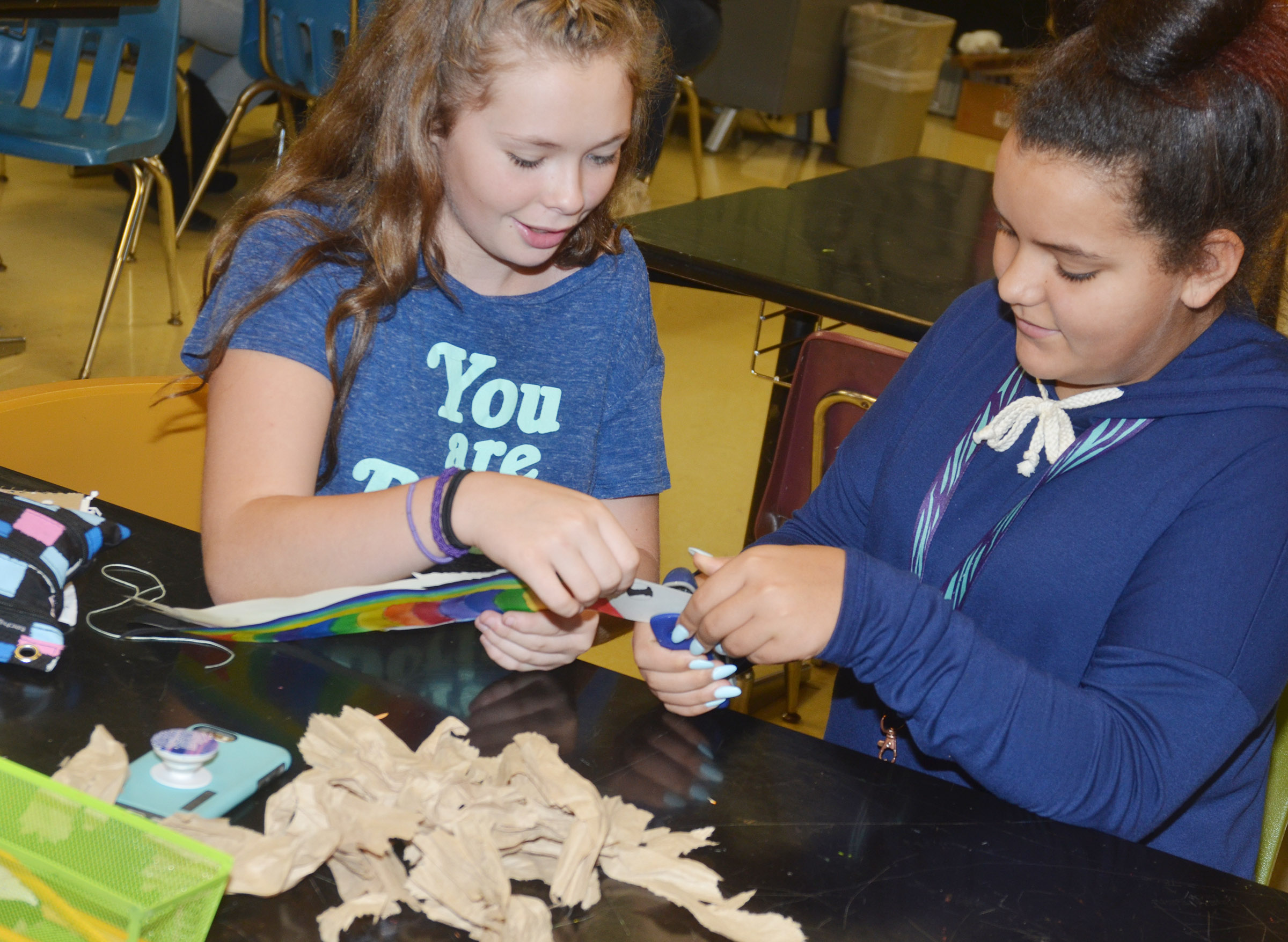 CMS sixth-graders CheyAnn Edwards, at left, and Gracie Taylor staple their koinobori together.
