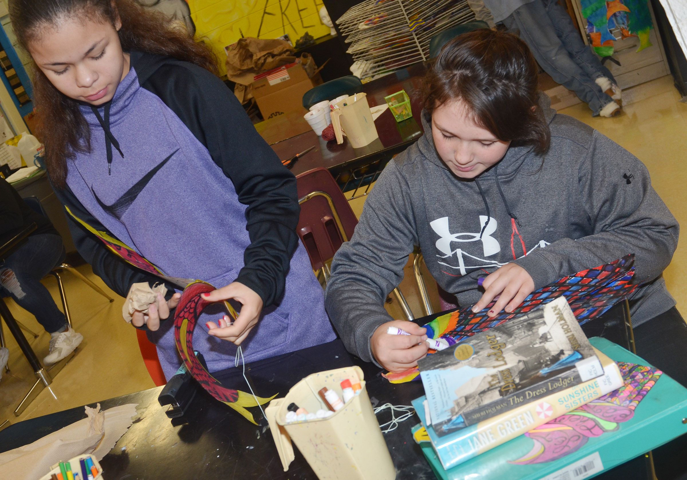 CMS sixth-grader Jayla Penn, at left, stuff hers koinobori as classmate Allie Compton colors hers.