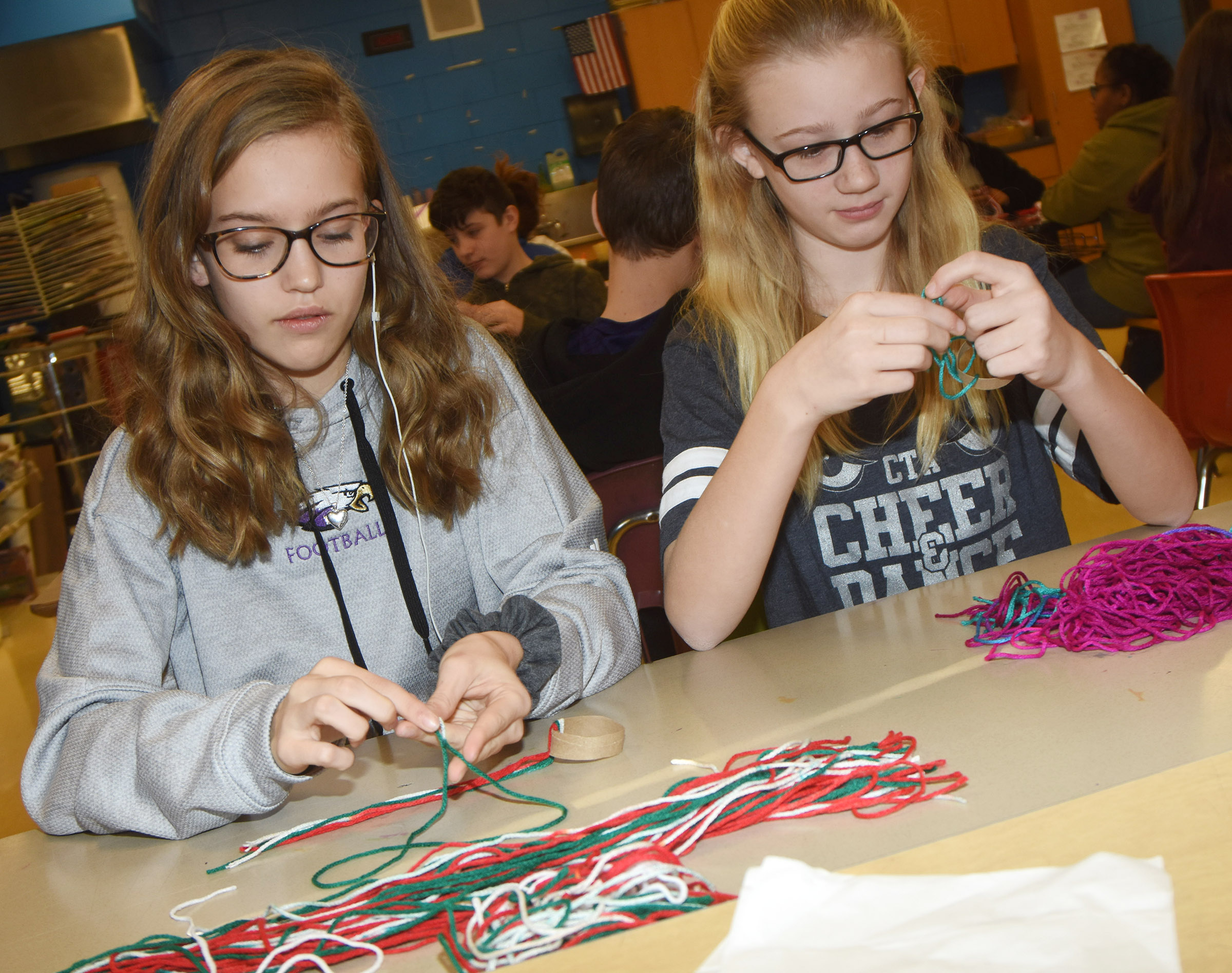 CMS seventh-grader Chloe Thompson, at left, and sixth-grader Vallie Houk make their hats.
