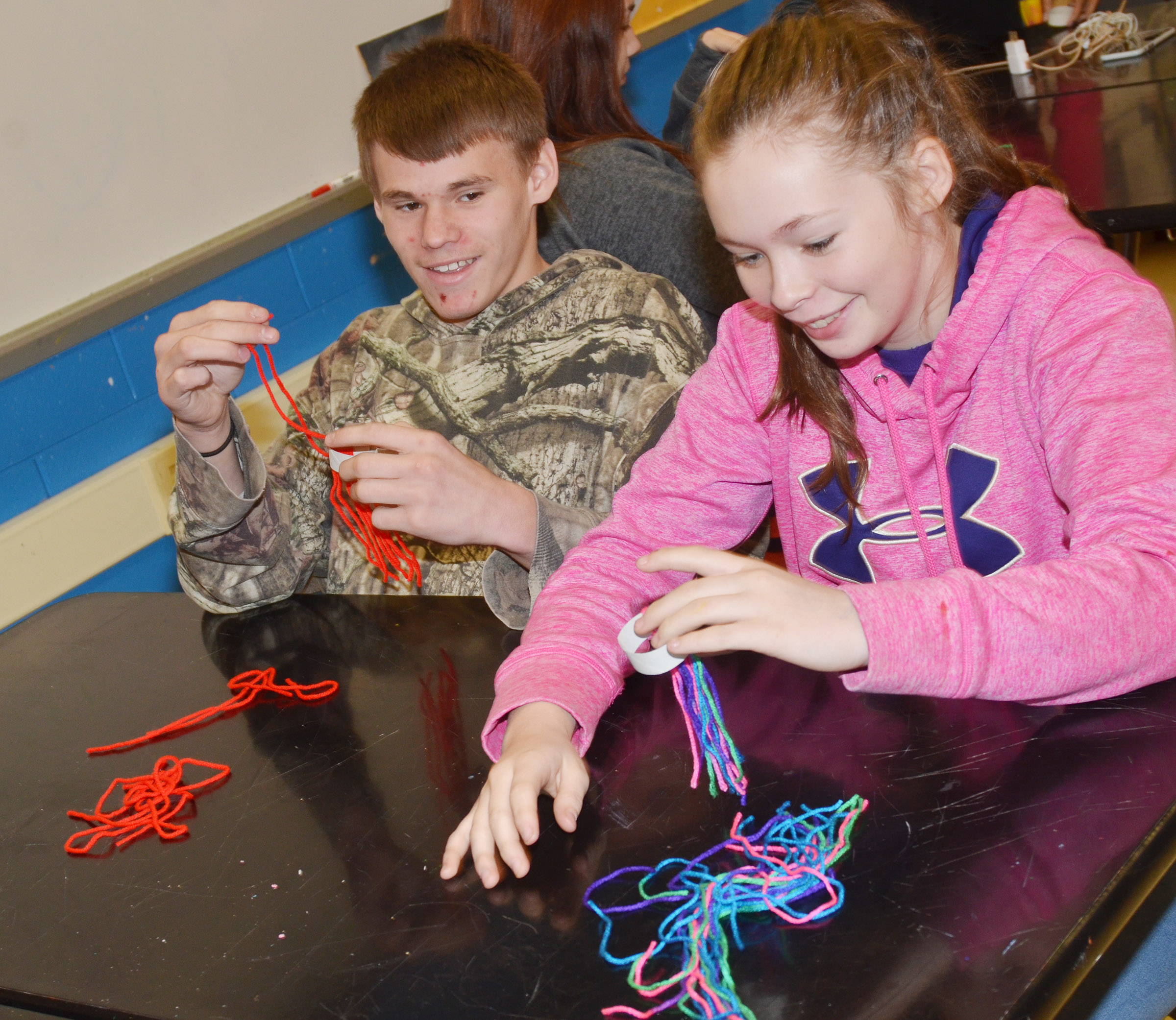 CMS eighth-grader Dalton Reynolds, at left, and sixth-grader CheyAnn Edwards use yarn to make miniature toboggans.