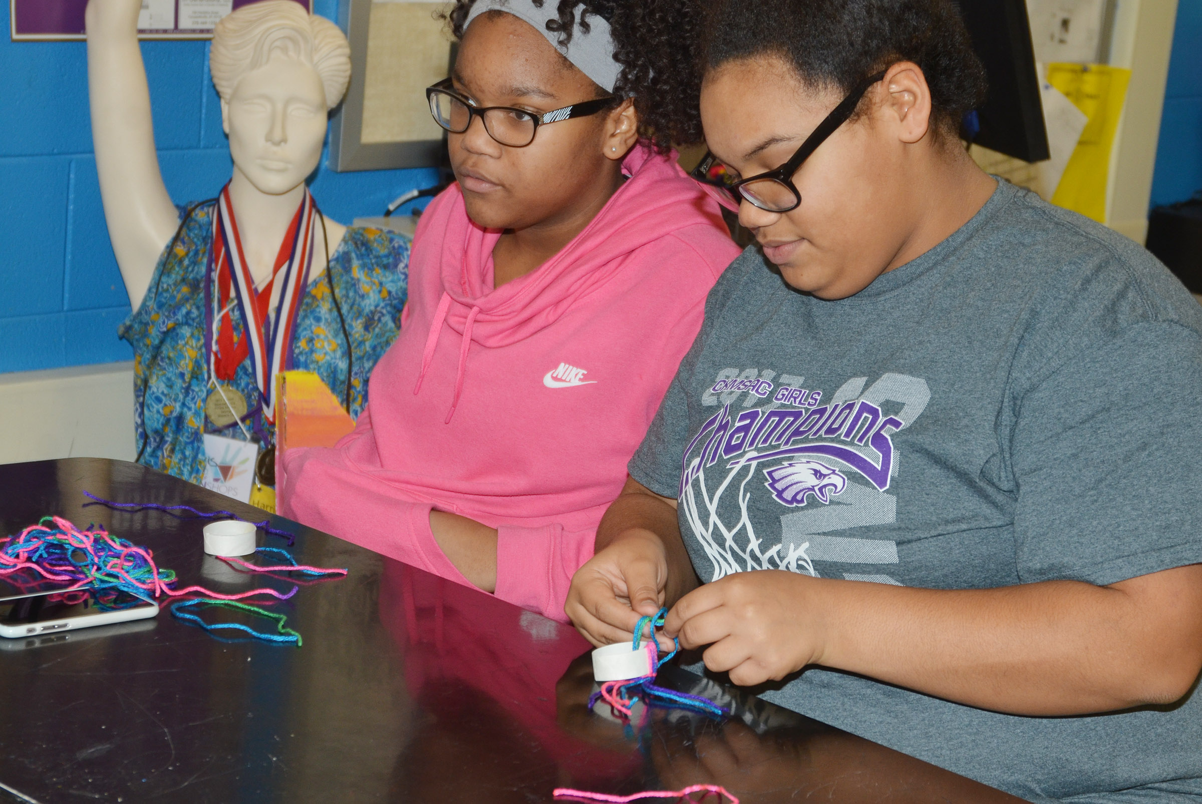 CMS seventh-grader Antaya Epps, at left, and eighth-grader Brae Washington use yarn to make miniature toboggans.