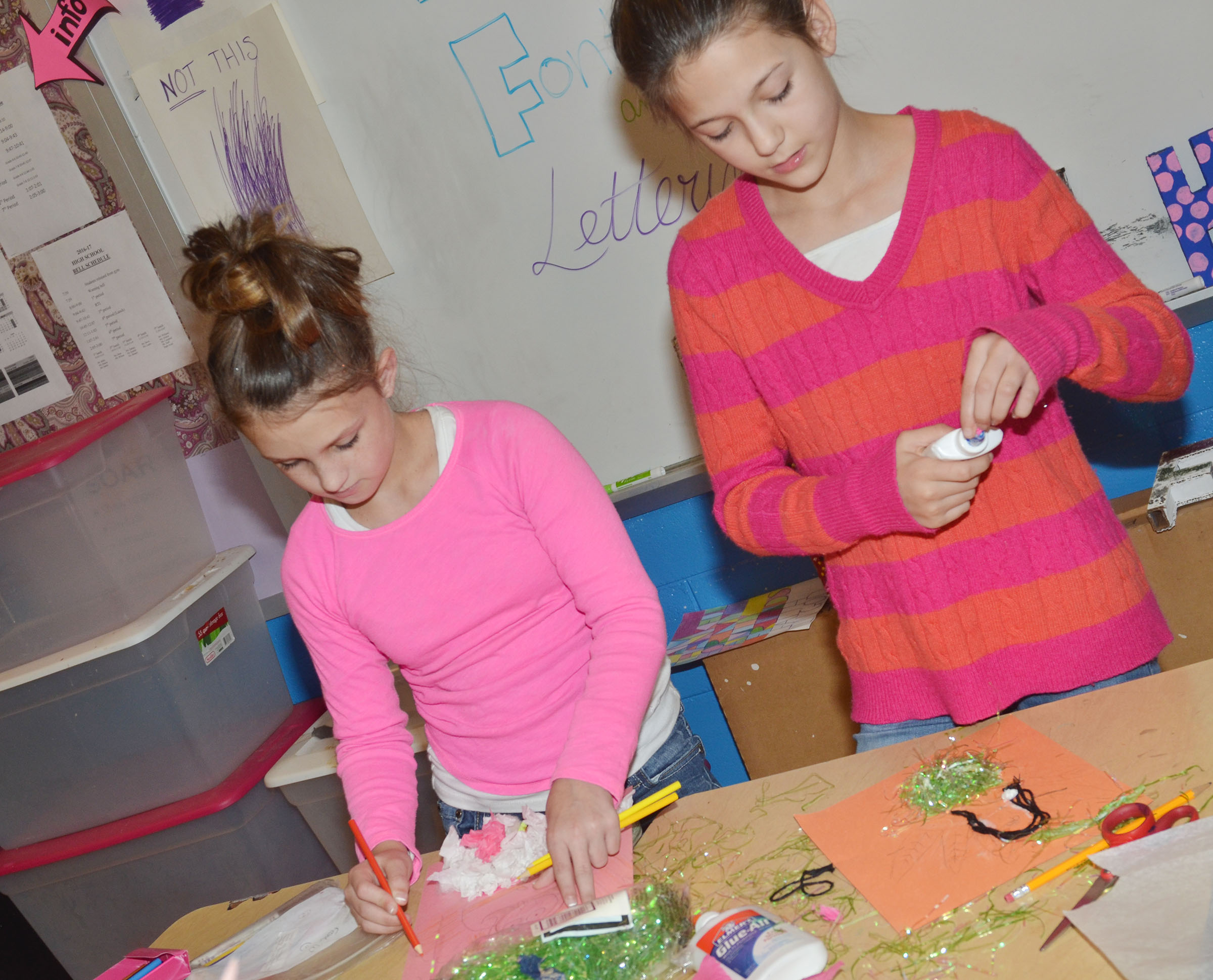 CMS fifth-graders Alexis Byers, at left, and Emily Shuck disguise their turkeys.