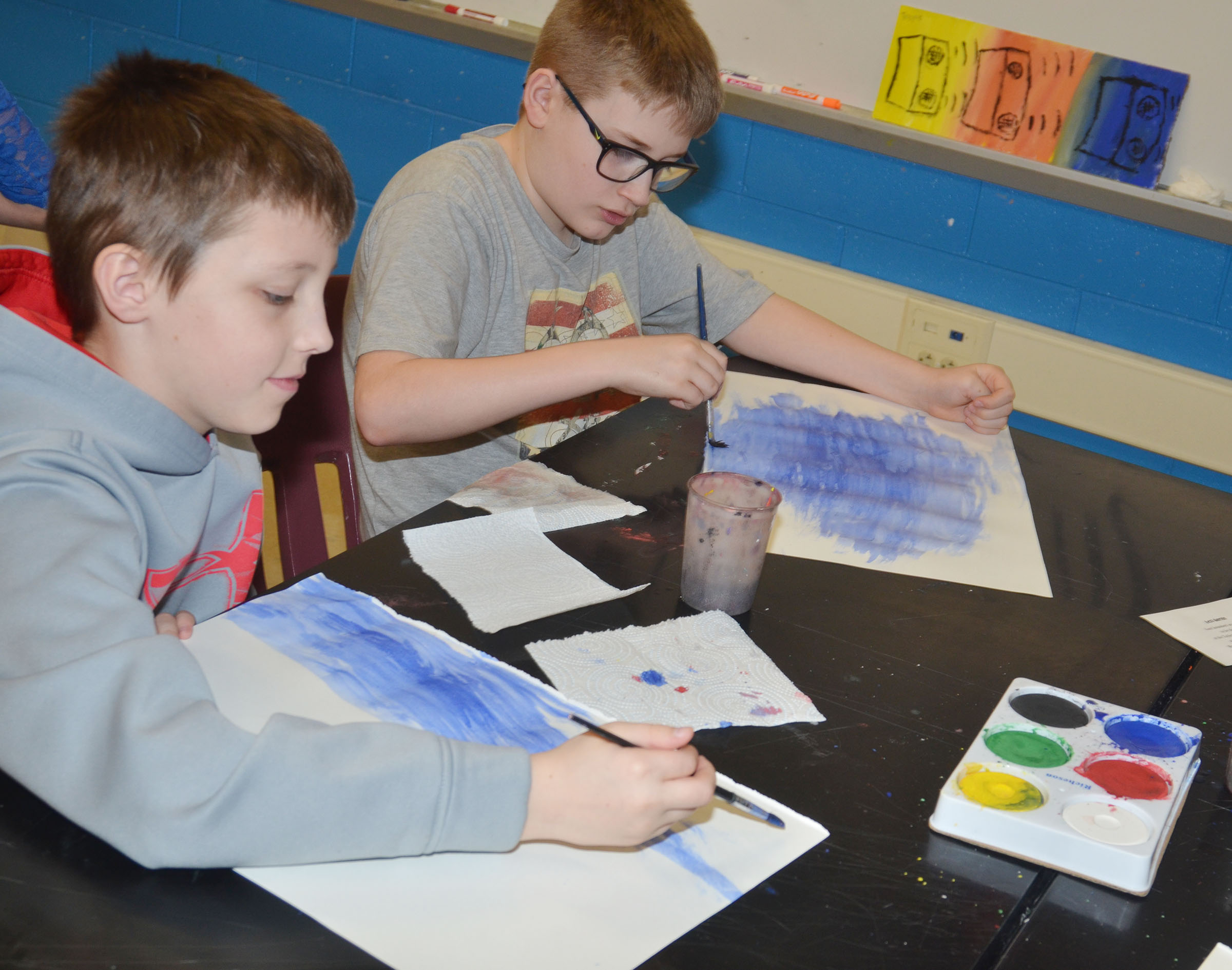CMS fourth-grader Jaxon Garrett, at left, and sixth-grader Brady Hoosier paint their Monet-inspired artwork.