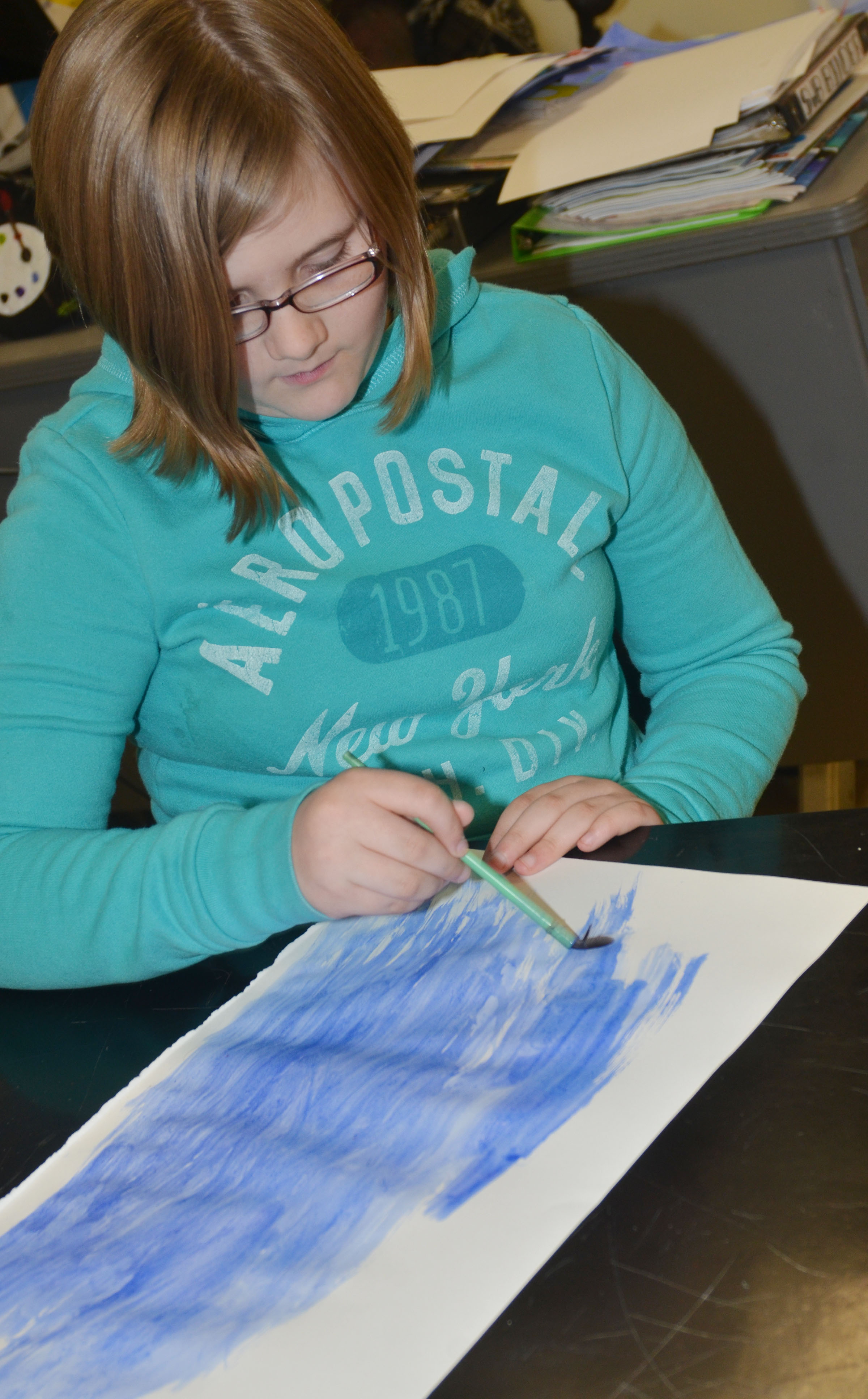 CMS fourth-grader Destiny Lane paints her Monet-inspired artwork.