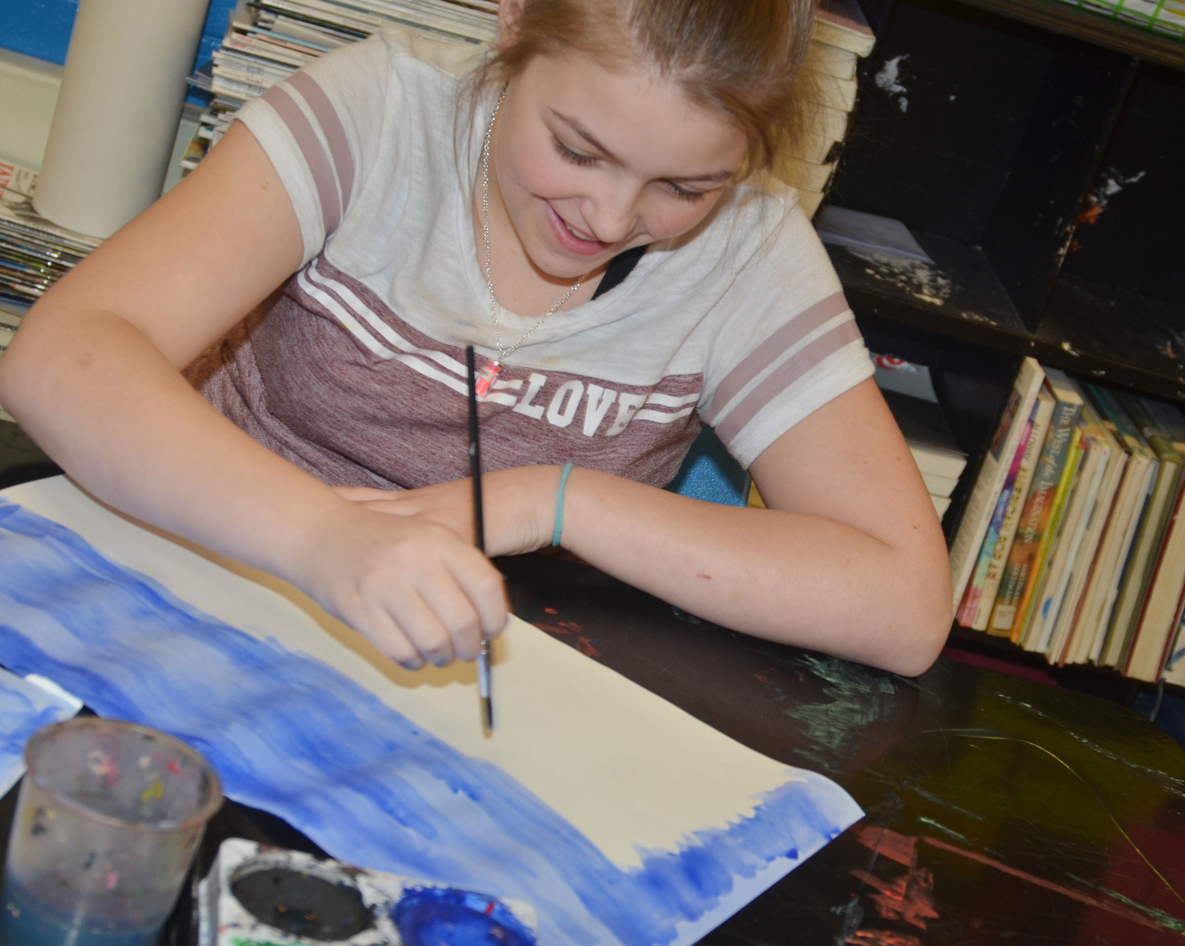 CMS fifth-grader Angel Walker paints her Monet-inspired artwork.