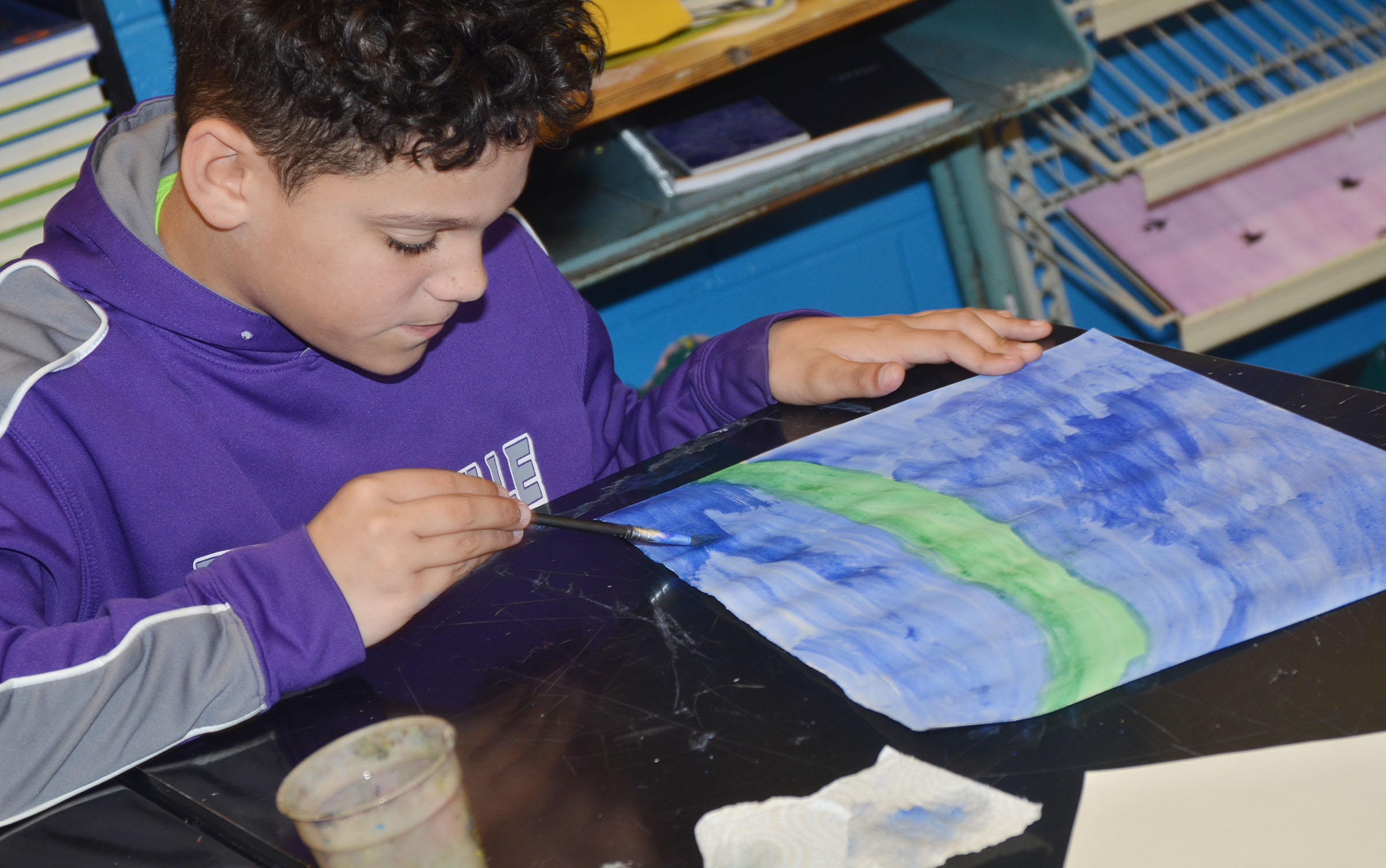 CMS sixth-grader Kaydon Taylor paints his Monet-inspired artwork.