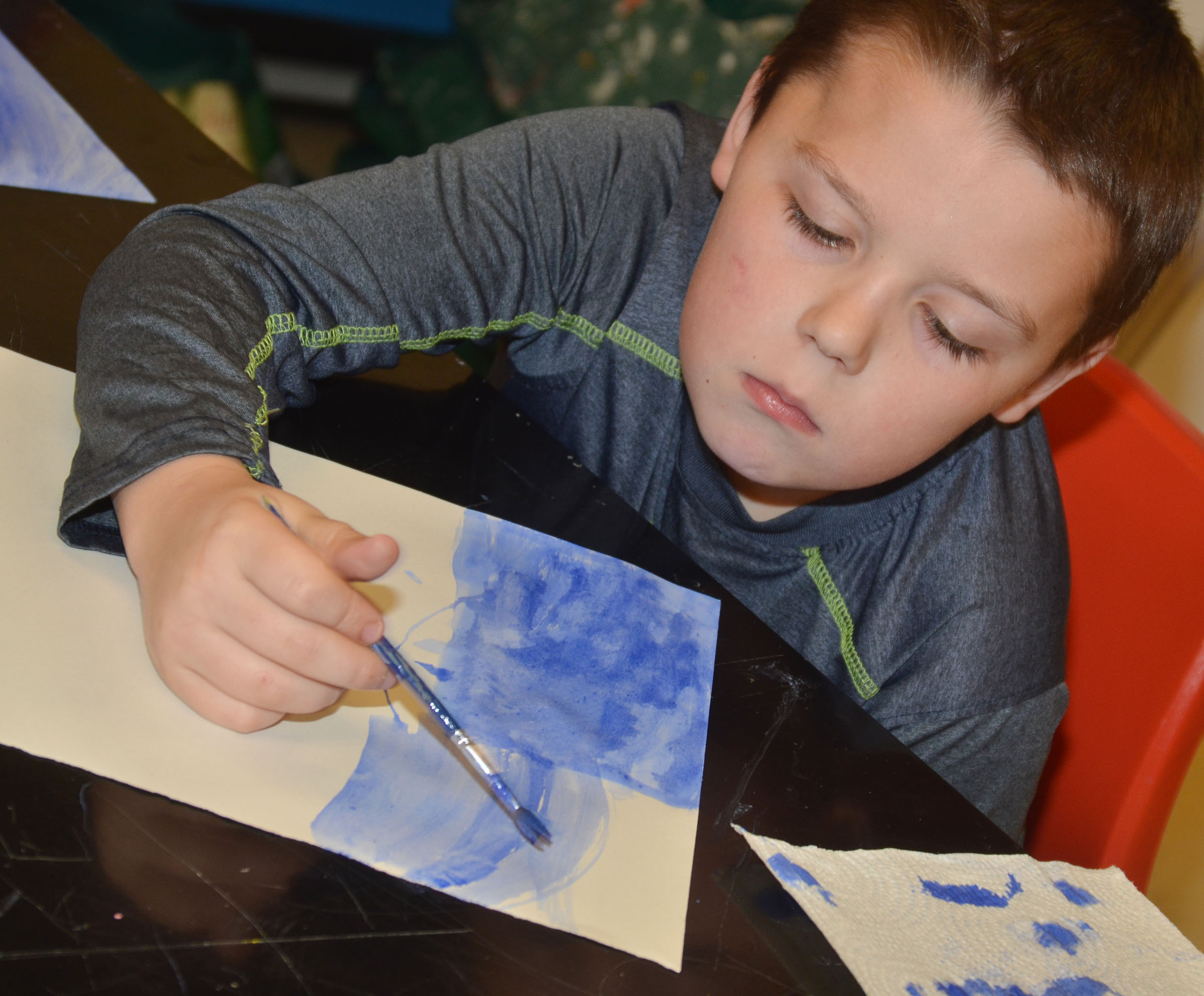 CMS fourth-grader Harley Underwood paints his Monet-inspired artwork.