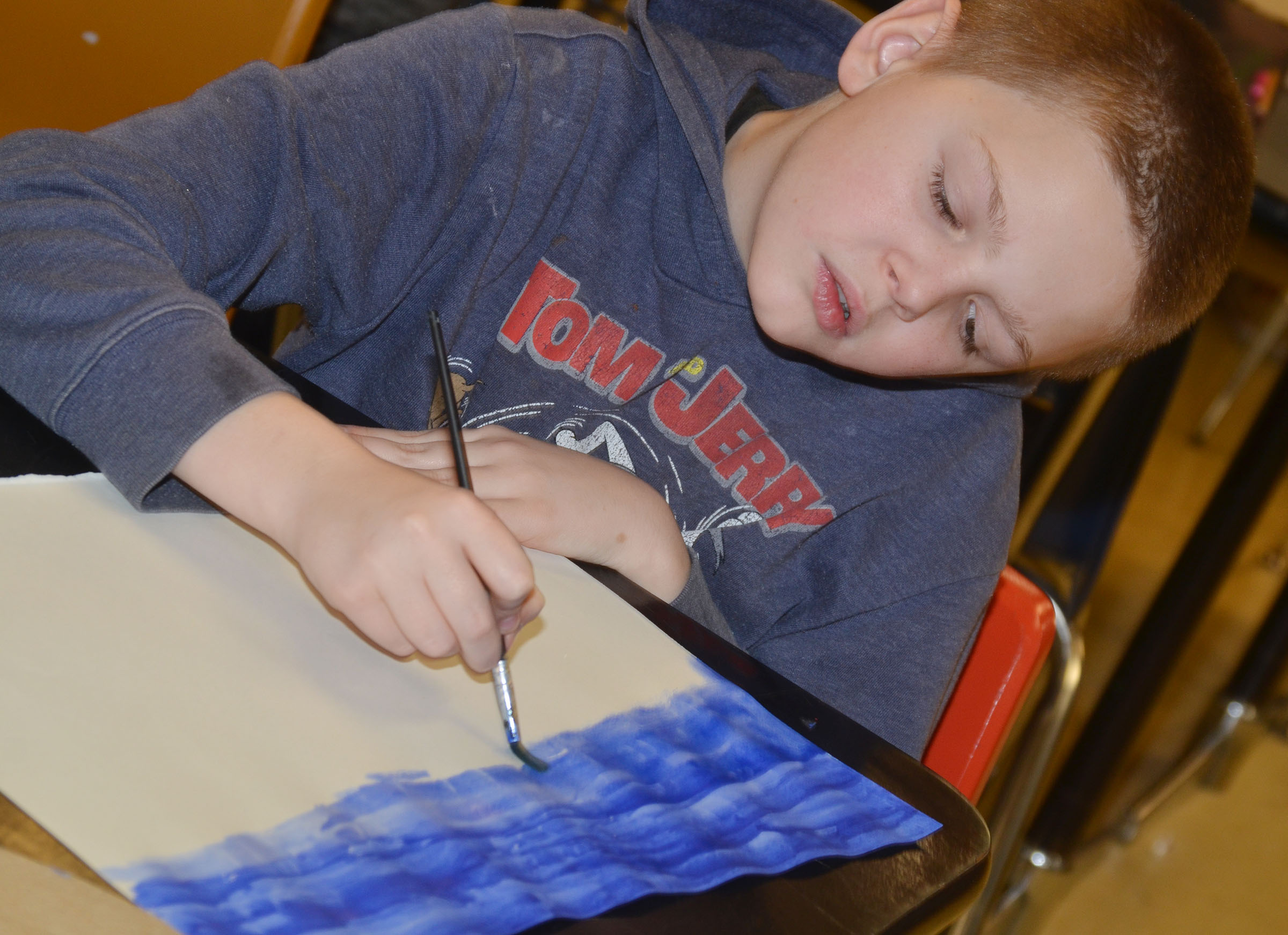 CMS fifth-grader Alex Jones paints his Monet-inspired artwork.