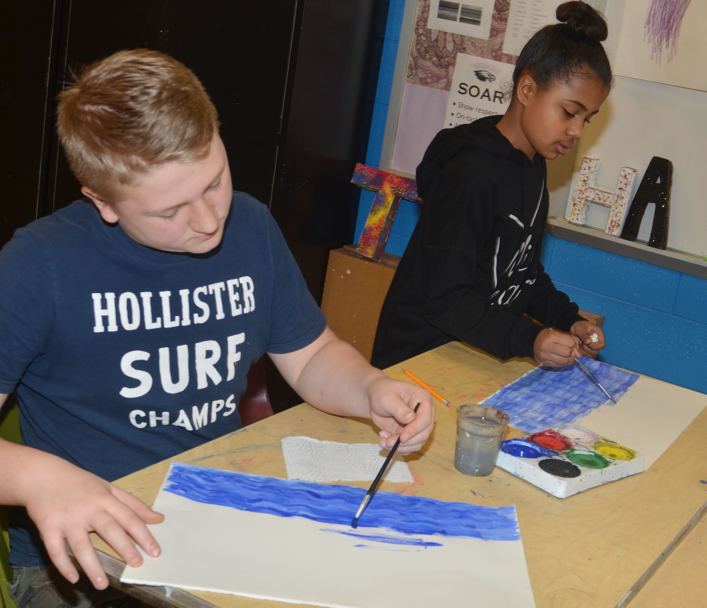 CMS sixth-grader Levi Dicken, at left, and fifth-grader Kendra Coulter paint their Monet-inspired artwork.