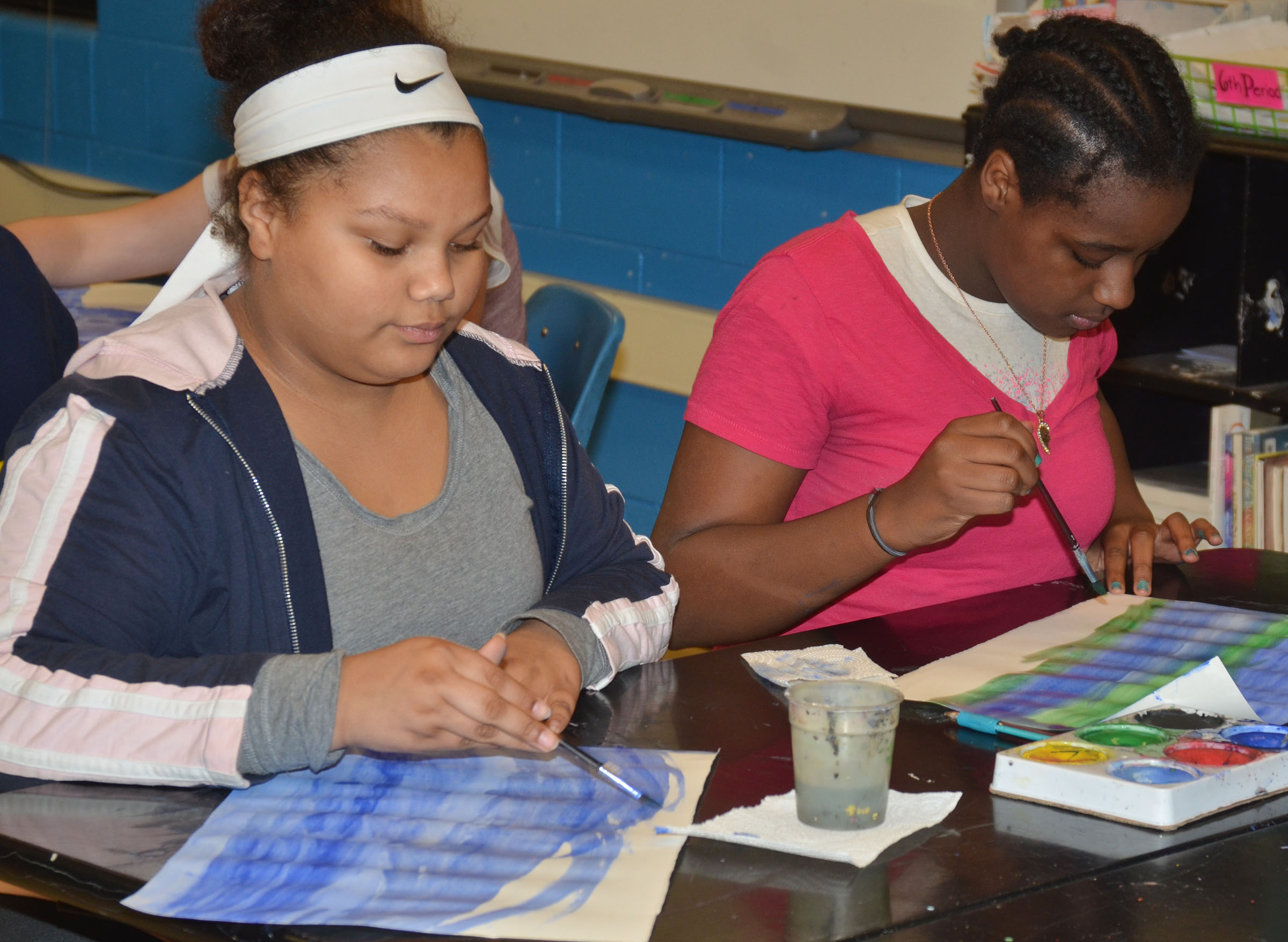 CMS sixth-grader Brooklyn Taylor, at left, and fifth-grader Hennessy Smith paint their Monet-inspired artwork.