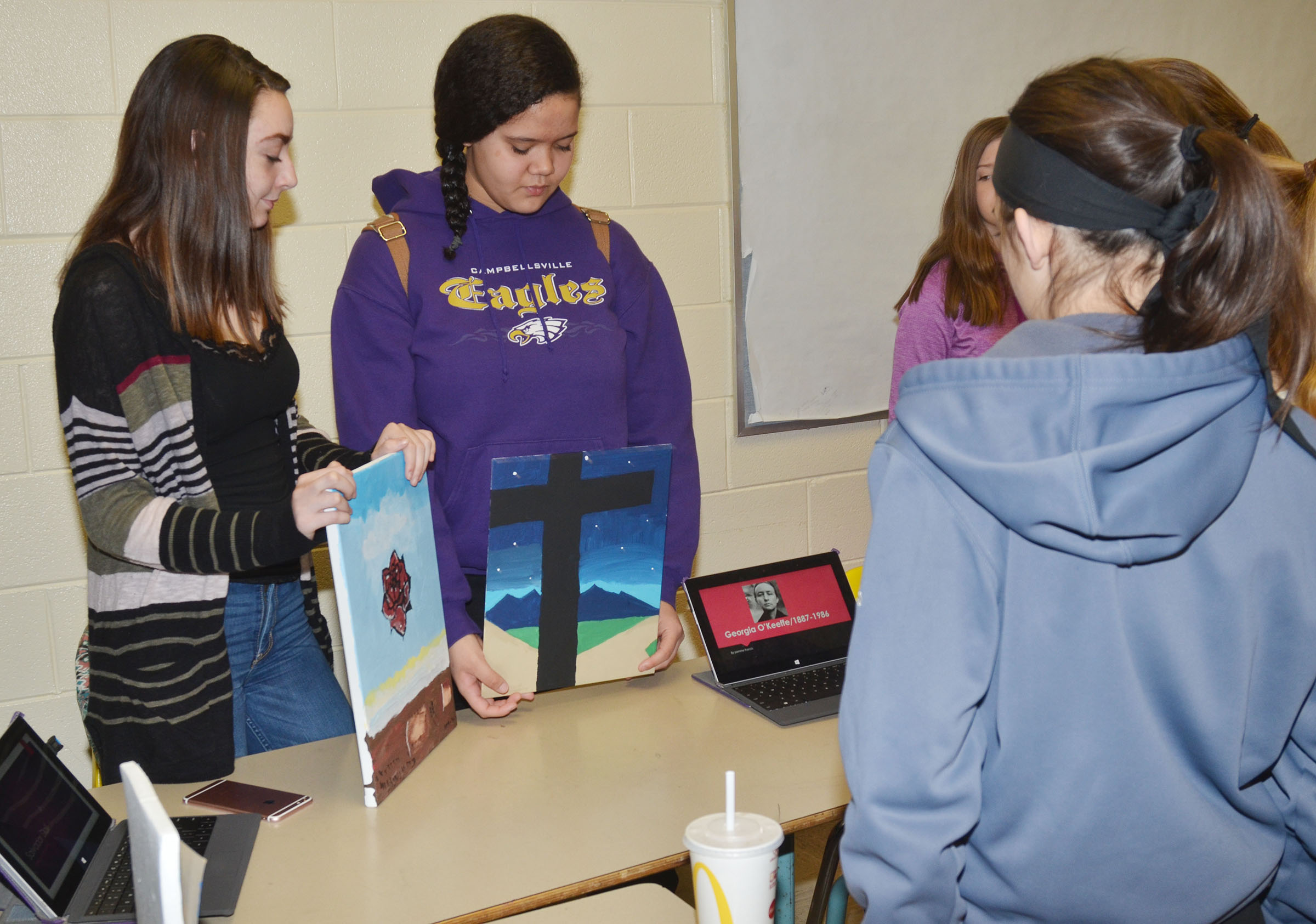 CMS eighth-graders Winter Mershon, at left, and Jasmine Francis display their artwork.