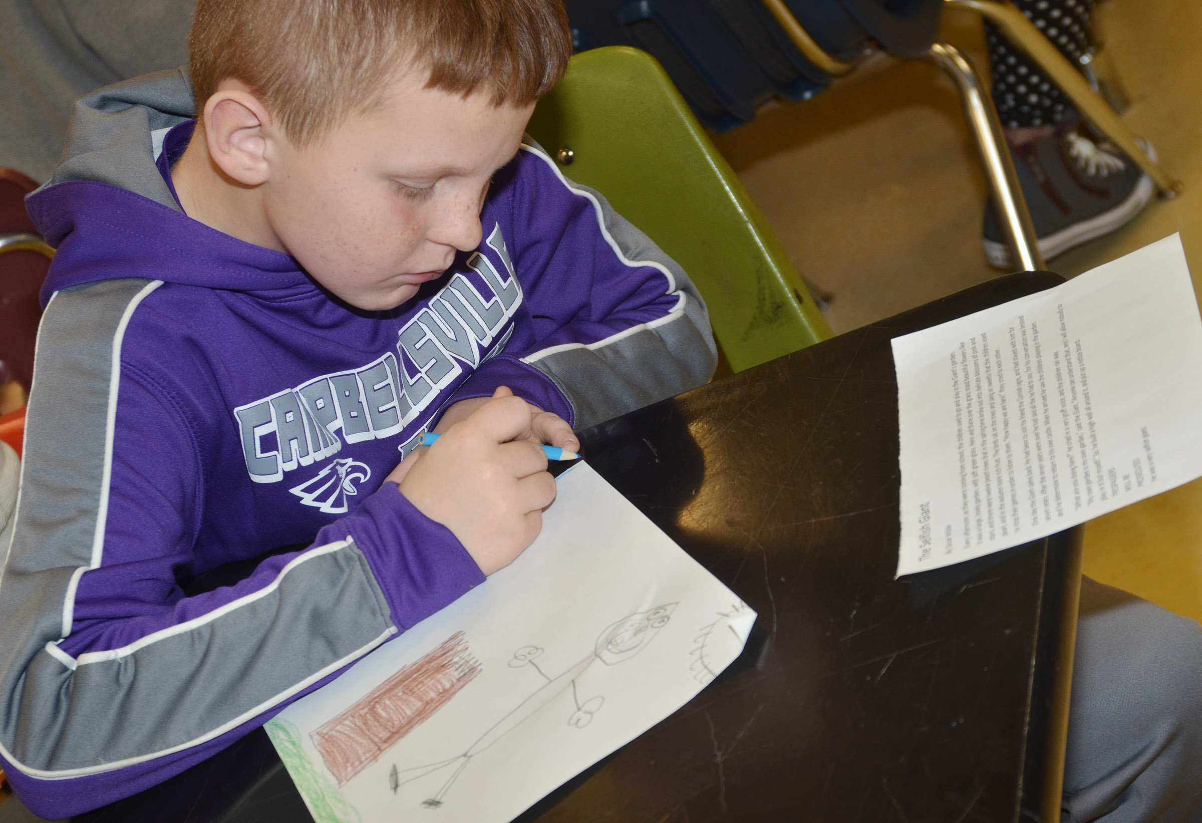 "CMS fifth-grader Jason Jeffries draws a pictured based on the story ""The Selfish Giant"" by Oscar Wilde."