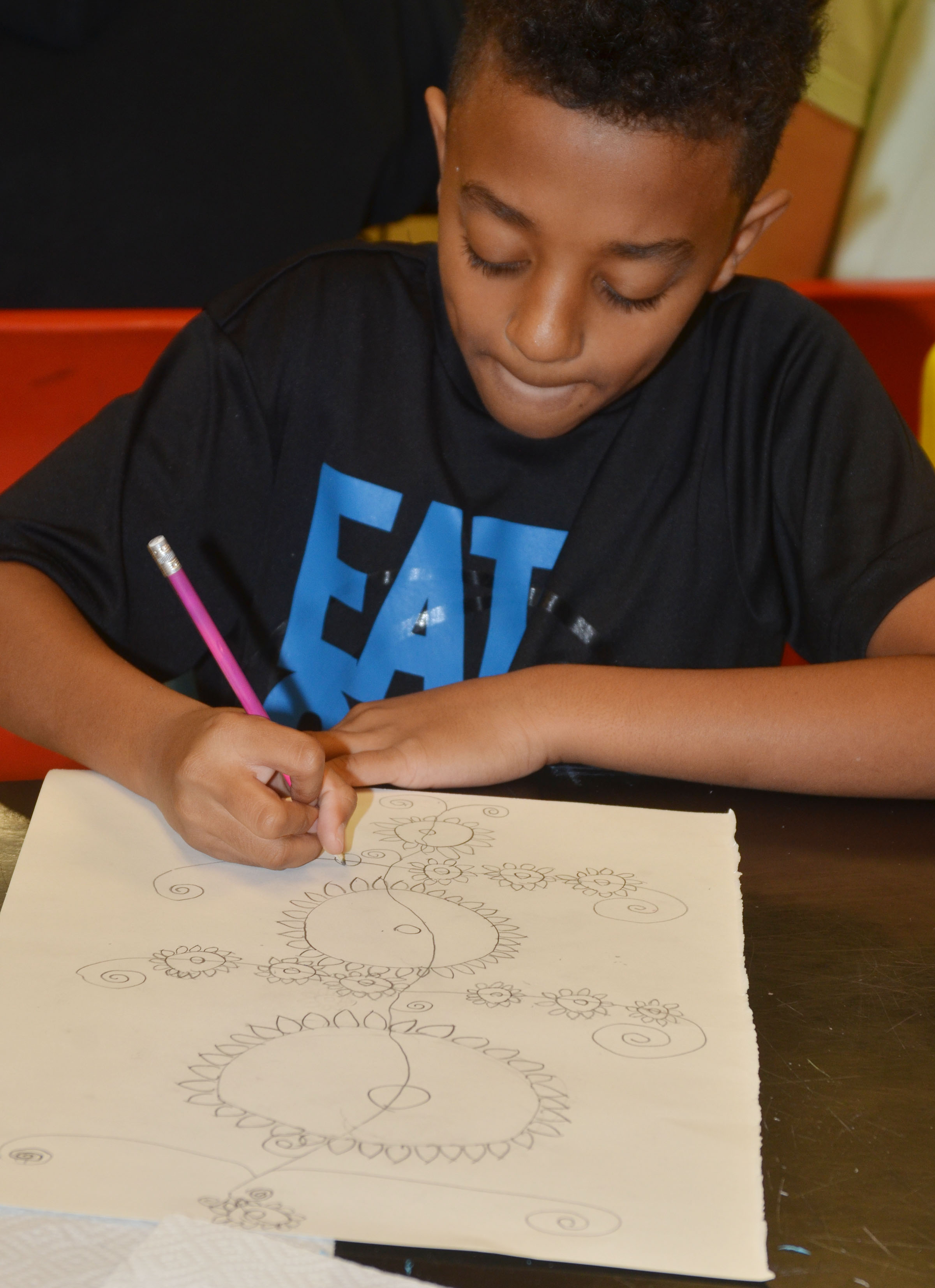 CMS sixth-grader Zamar Owens draws his flowers.