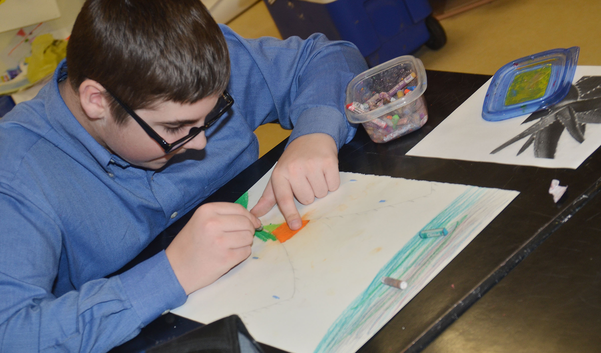 CMS eighth-grader Evan Henderson adds color to his flower drawing.