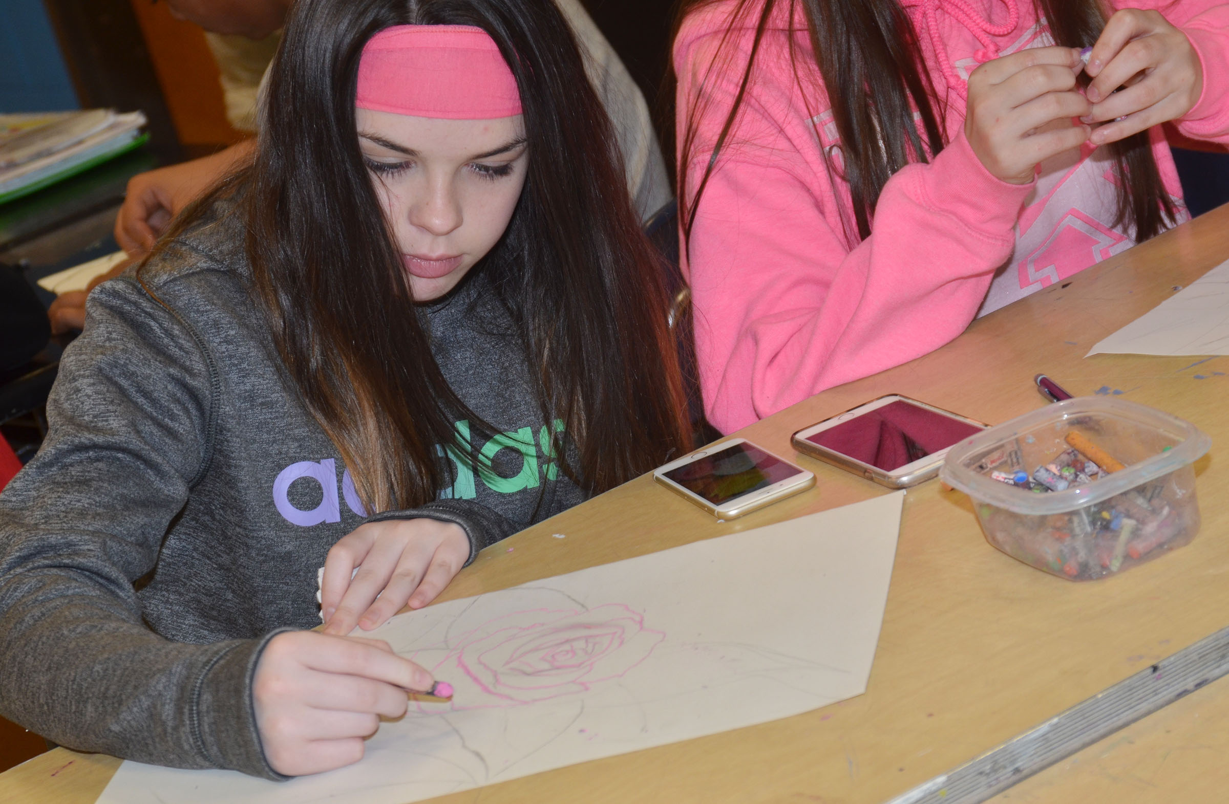 CMS seventh-grader Destiny Agee colors her flower drawing.