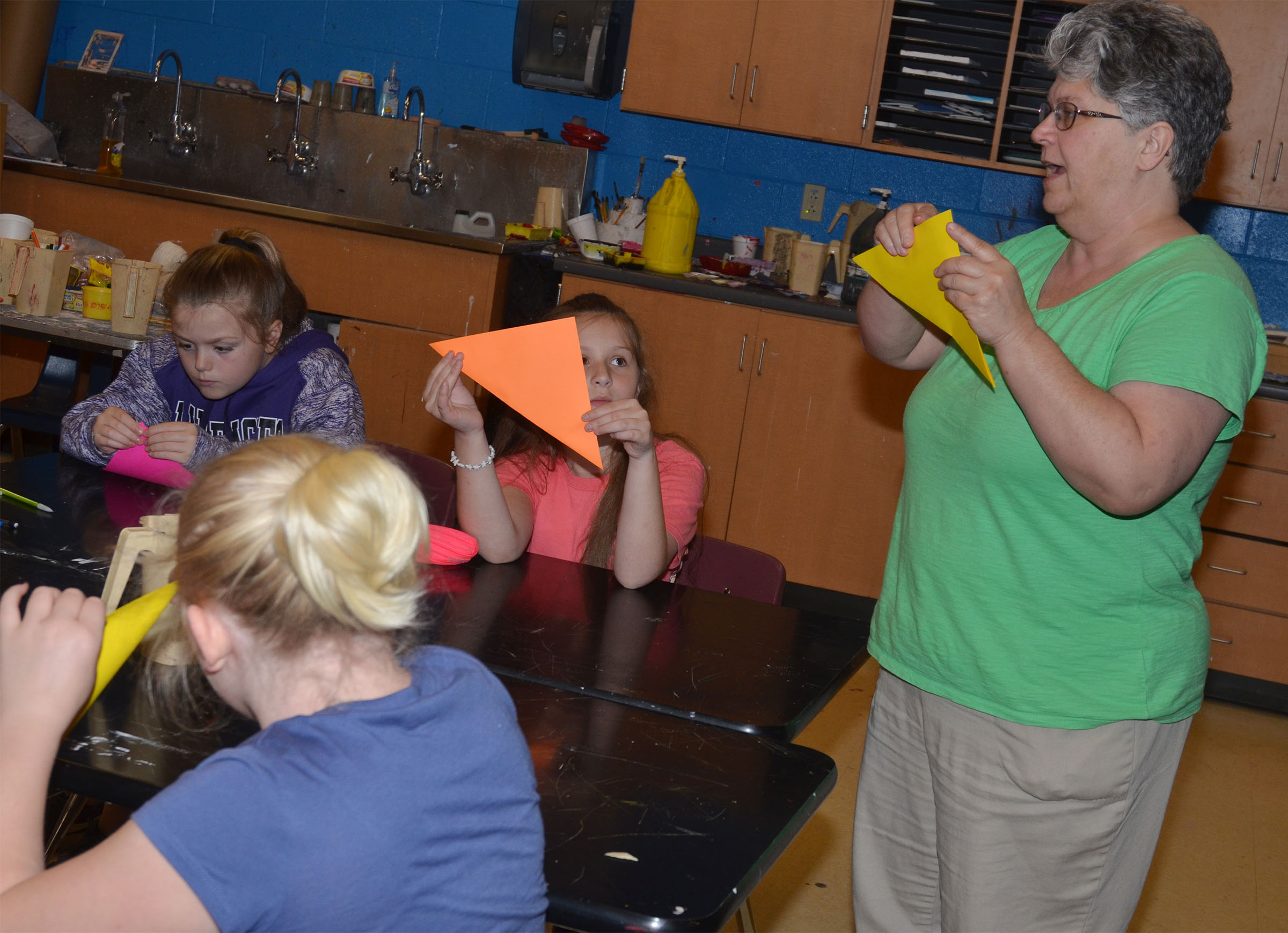 CMS art teacher Jo Ann Harris teaches her students to make an origami crane.