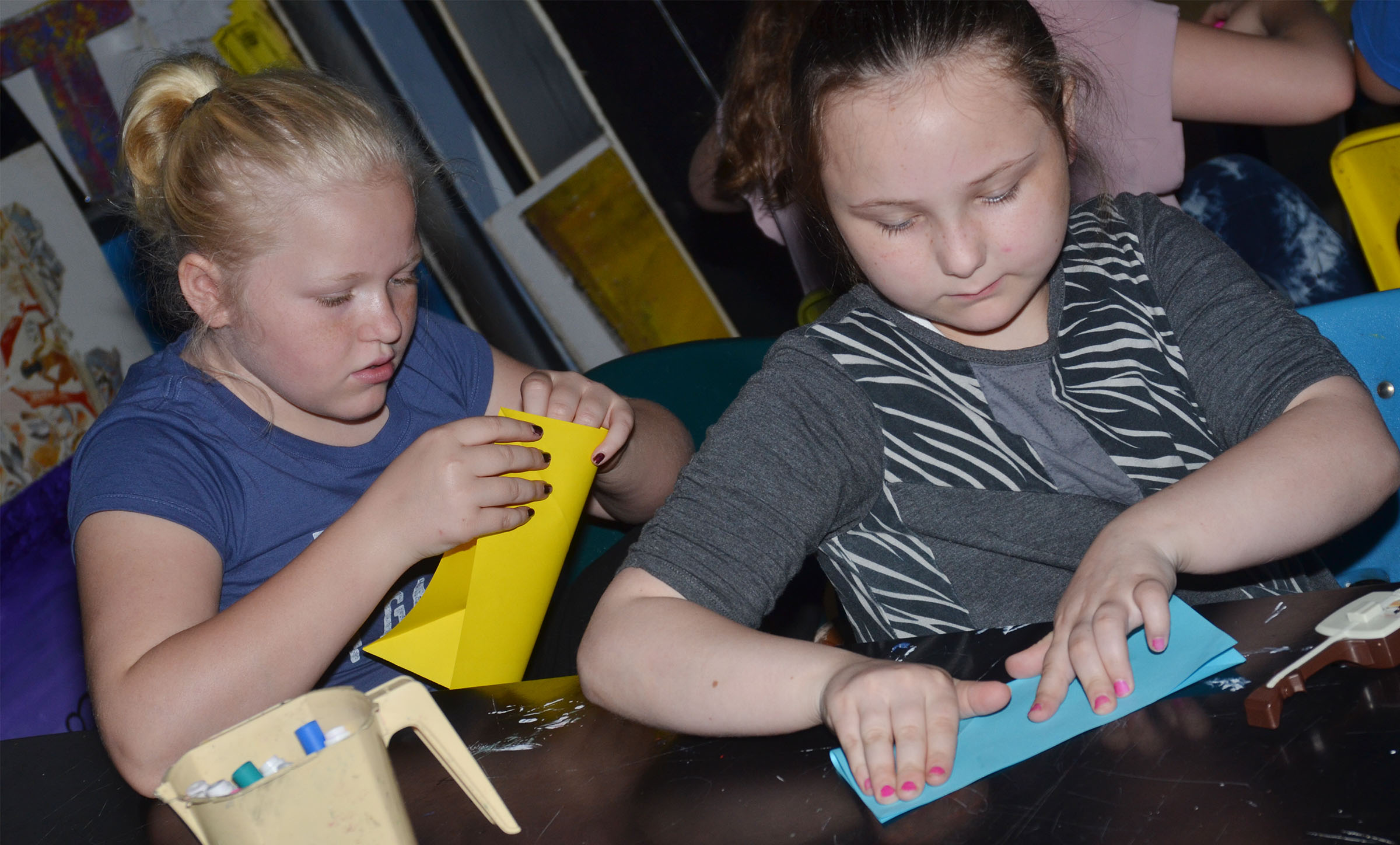 CMS fourth-graders Daisy Wilkerson, at left, and Shyanna Young make their cranes.