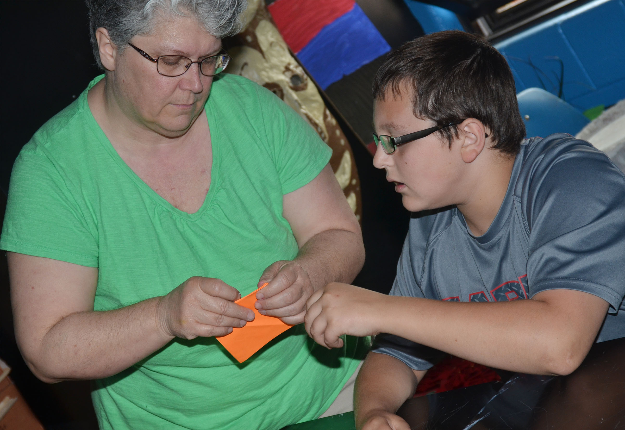 CMS art teacher Jo Ann Harris helps sixth-grader Cameron Mahan make his crane.