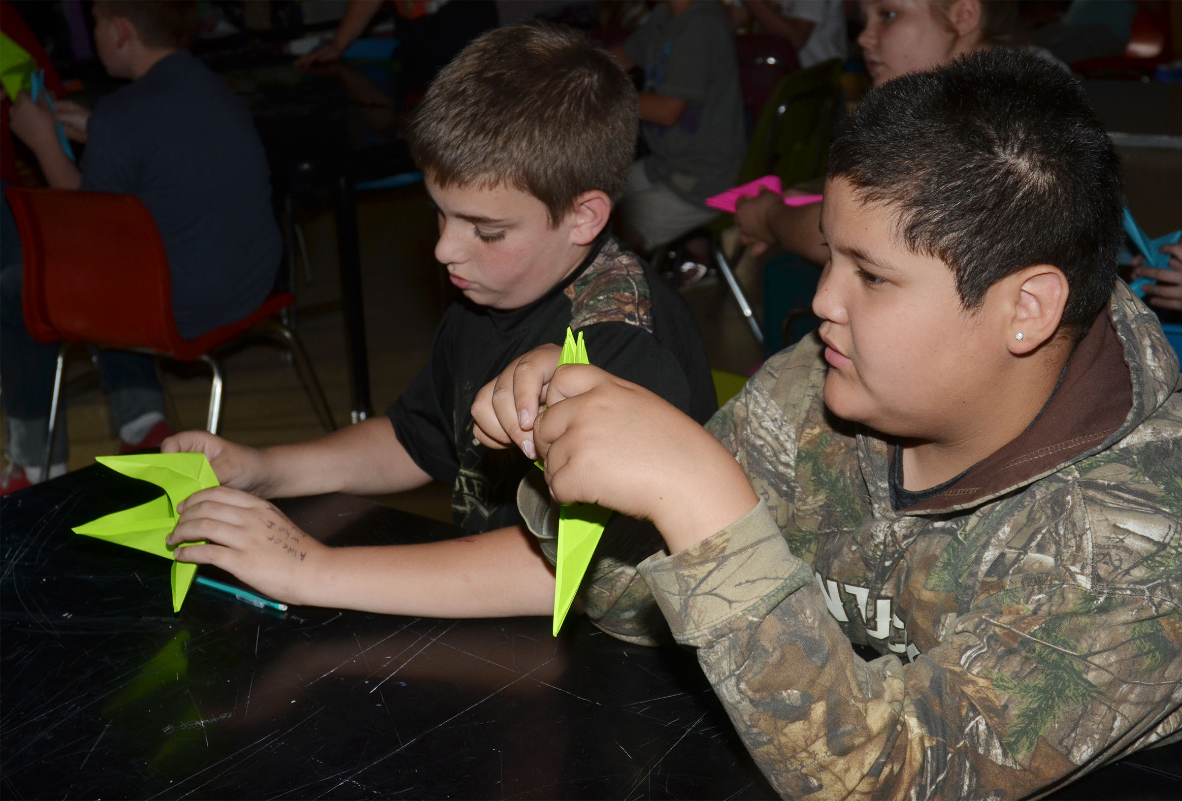 CMS fifth-graders Ashton Davis, at left, and Xavier Florez make their cranes.
