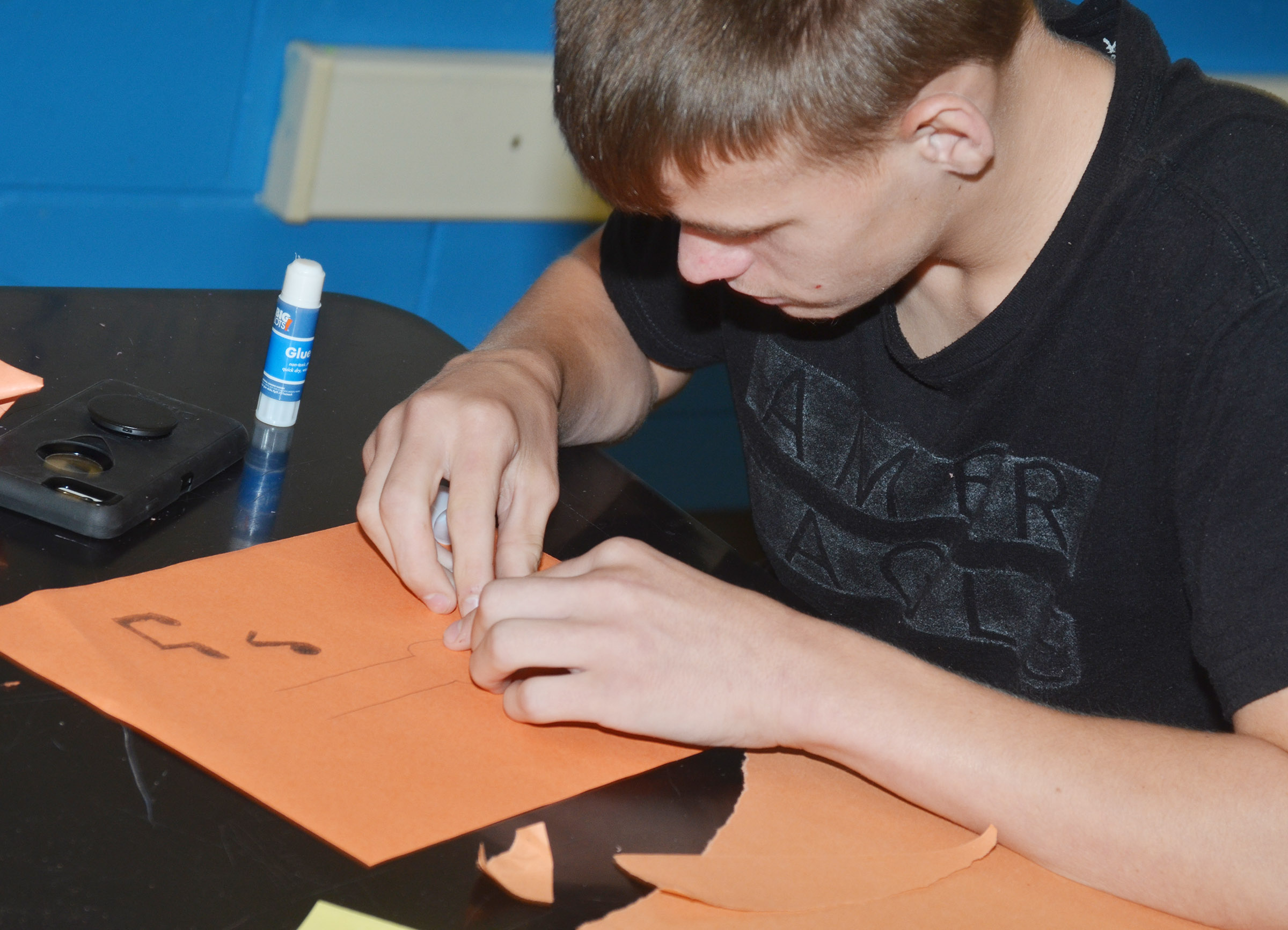 CMS eighth-grader Dalton Reynolds glues paper on his collage.