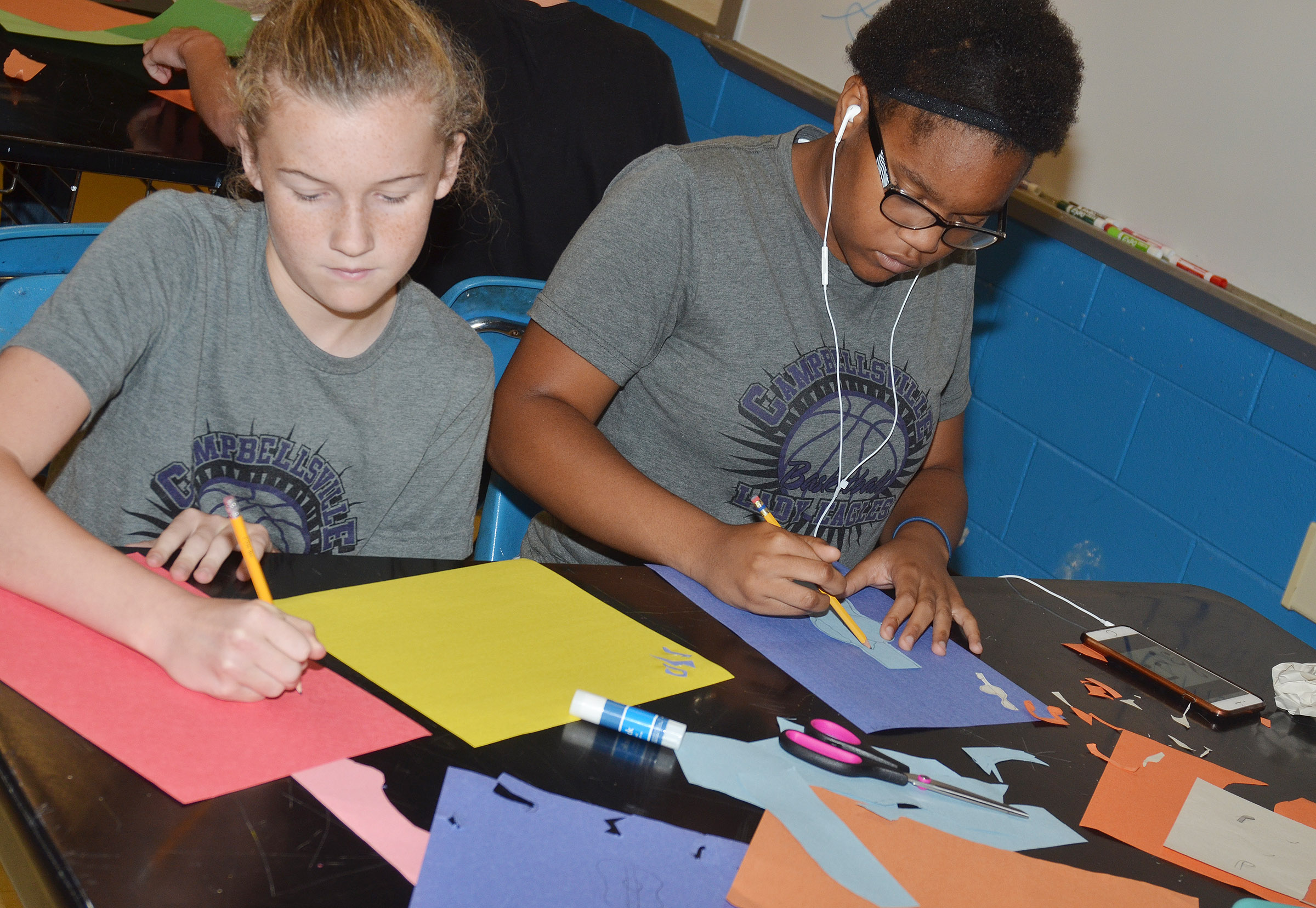 CMS seventh-graders Dakota Slone, at left, and Antaya Epps create their collages.