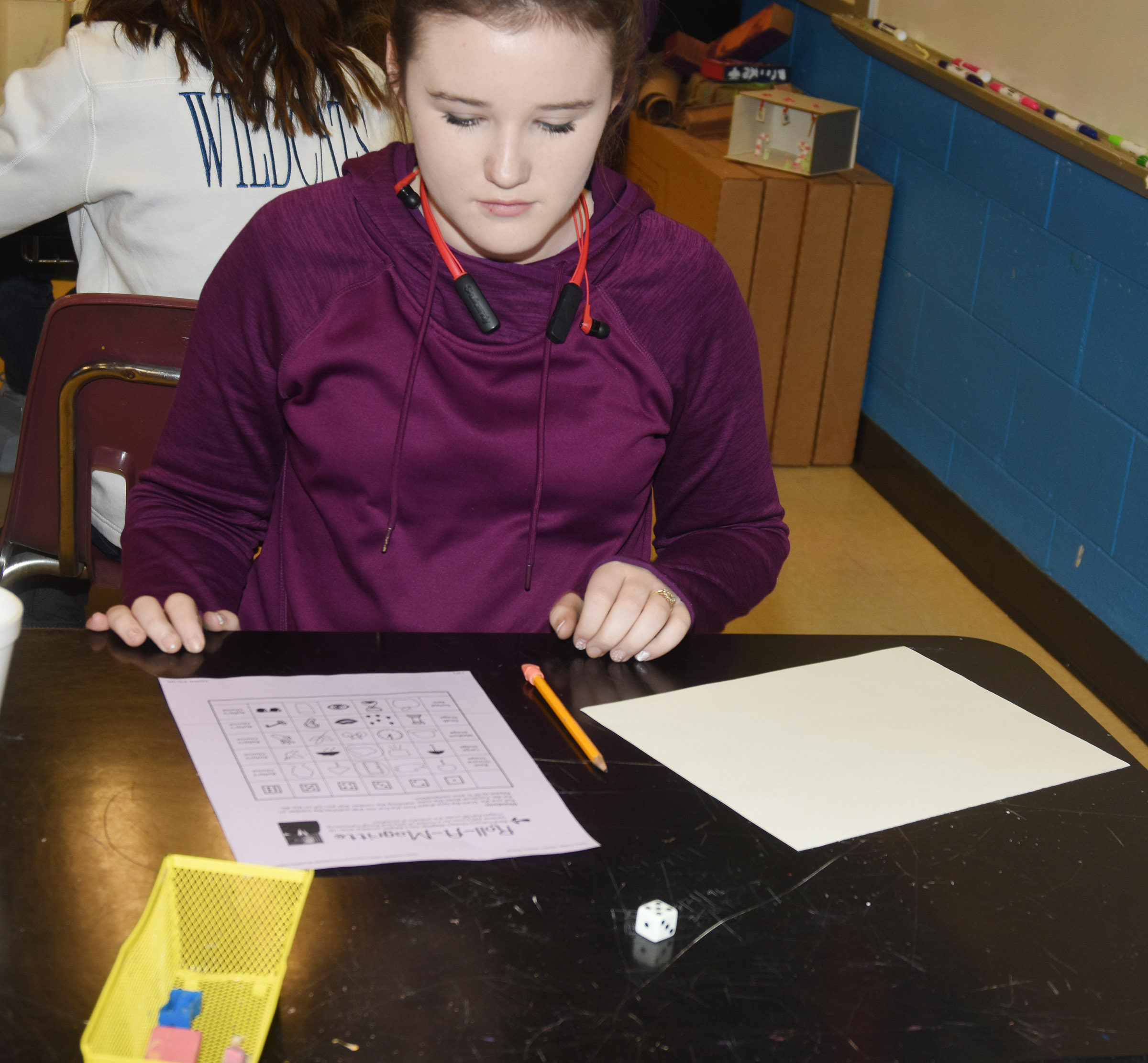 CMS eighth-grader Abby Brisko rolls a dice to see what objects she will use to create her surrealism artwork.