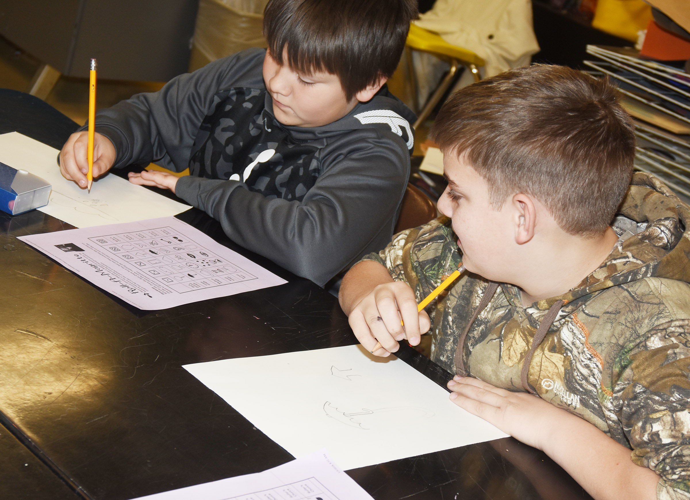 CMS sixth-graders Leo Lamer, at left, and Ashton Davis draw their surrealism artwork.