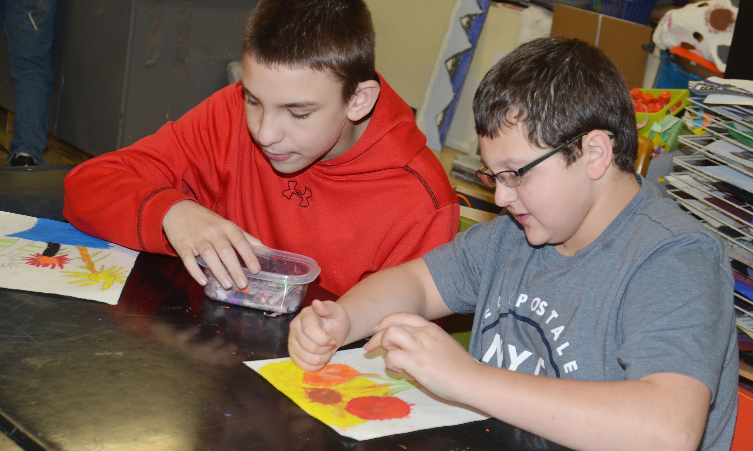 CMS sixth-graders Nate Mitchell, at left, and Cameron Mahan color their sunflower drawings.