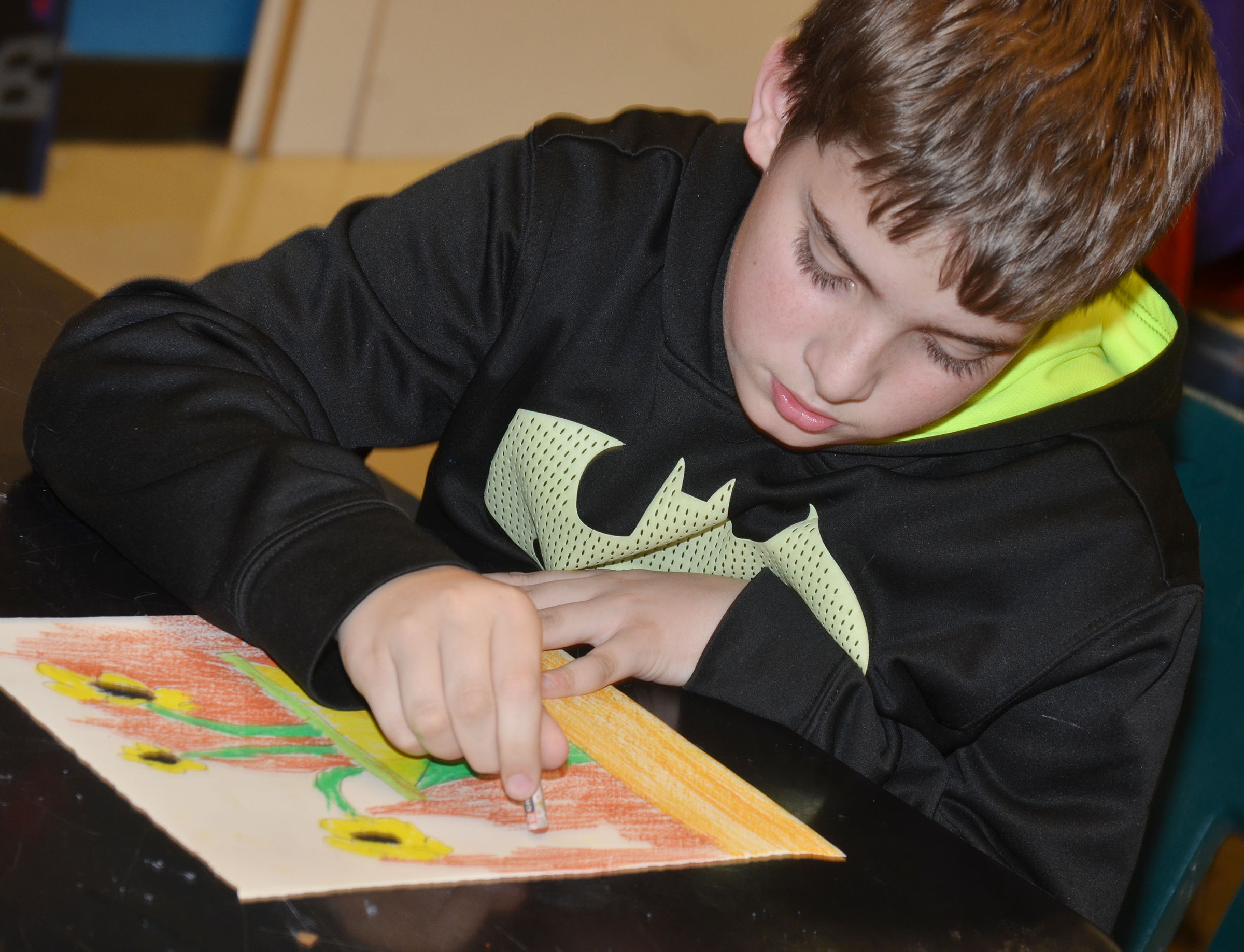 CMS fifth-grader Ashton Davis colors his sunflower drawing.