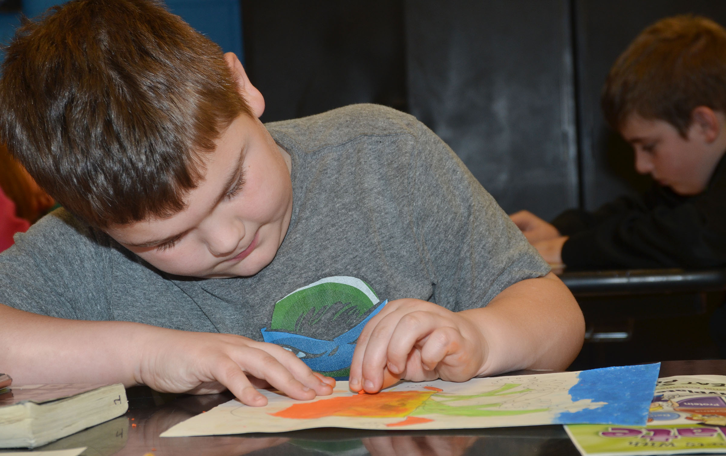 CMS fourth-grader Logan England colors his sunflower drawing.