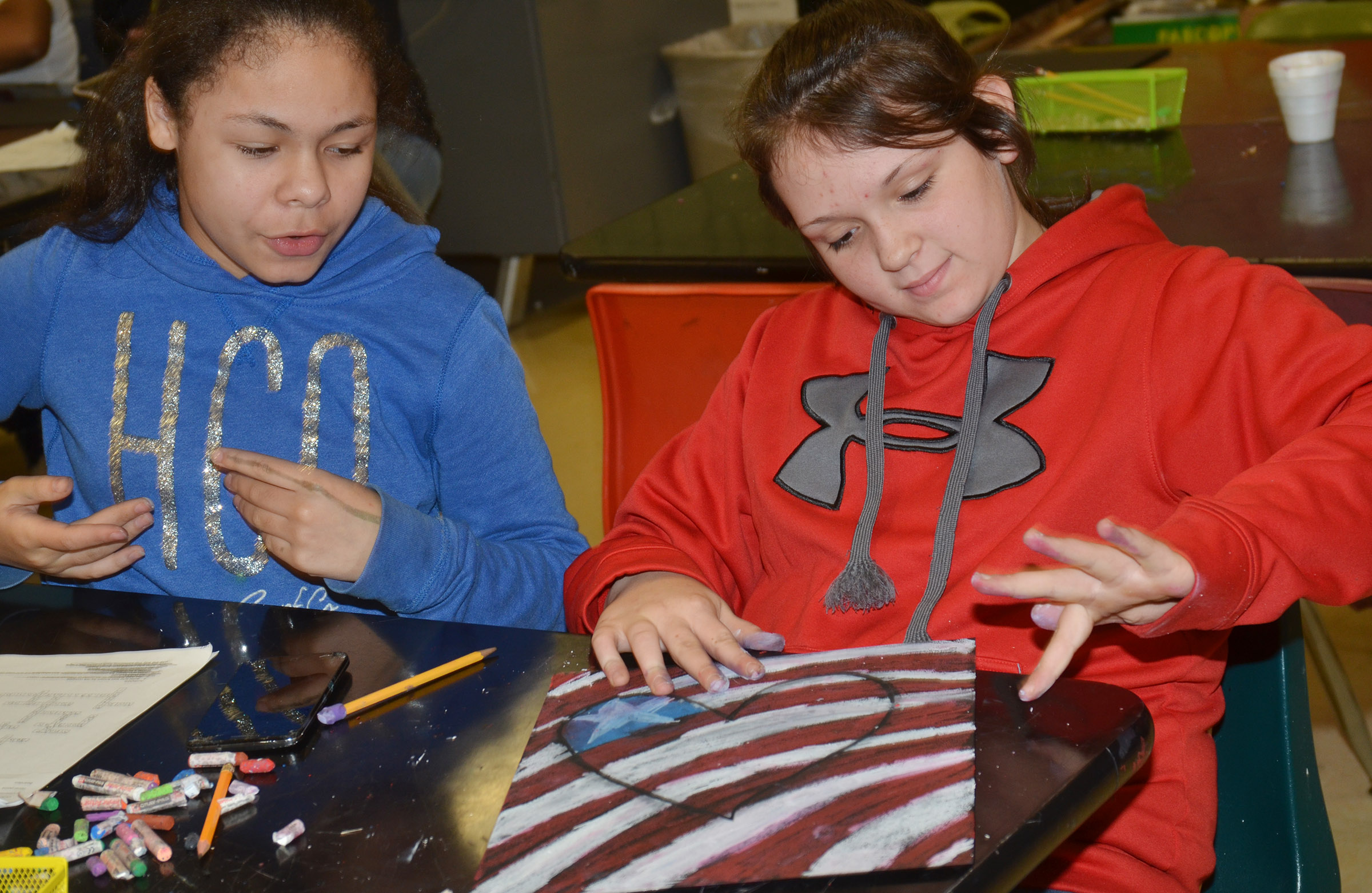 CMS sixth-graders Jayla Penn, at left, and Allie Compton talk as they add color to their hearts.