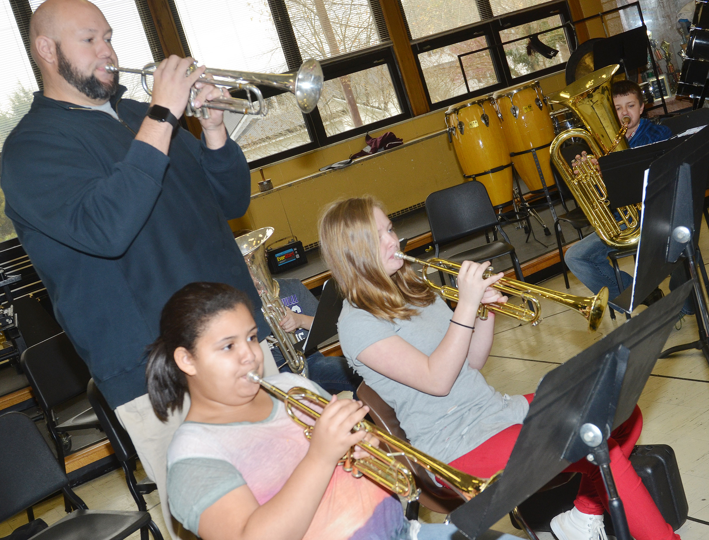CMS band director Zach Shelton plays along with, from left, sixth-grader Kyleigh Richerson and seventh-graders Davanna Reardon and Tyler Booth.
