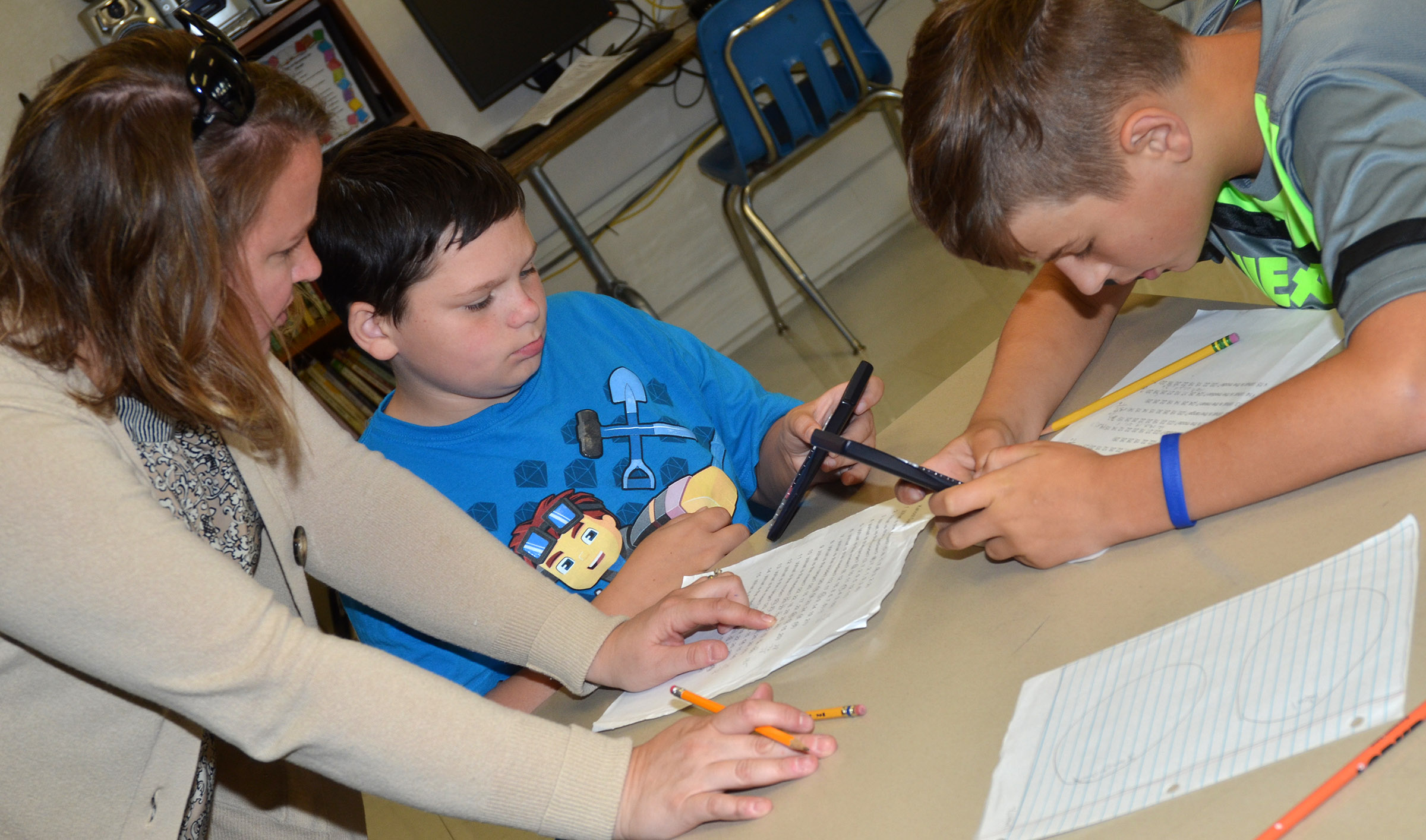 CMS teacher Katie Campbell helps sixth-graders Gregory Burton, at left, and Jaxon Sidebottom find the mode of a set of numbers.